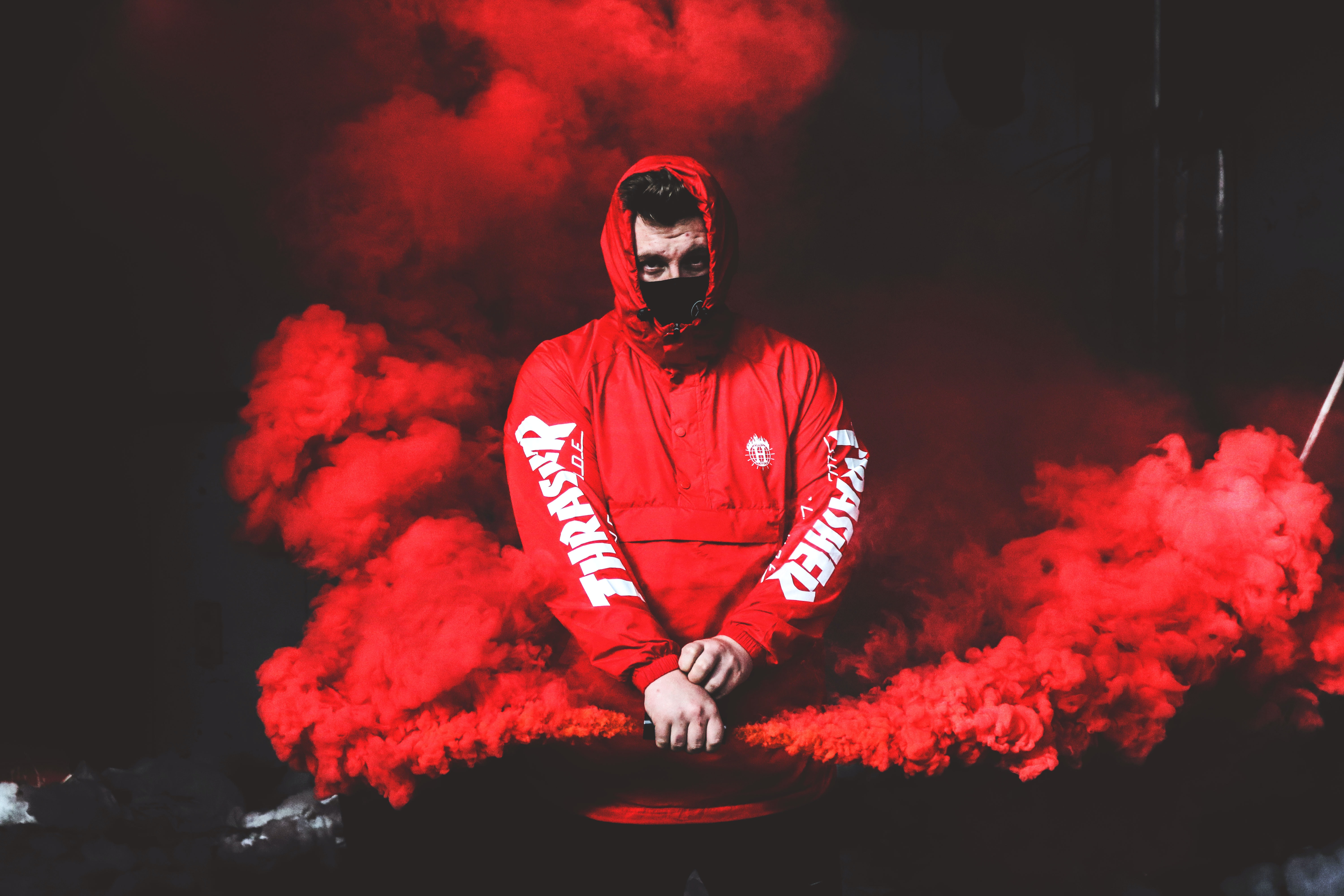 man wearing red and white hoodie and black mask surrounded by red smoke