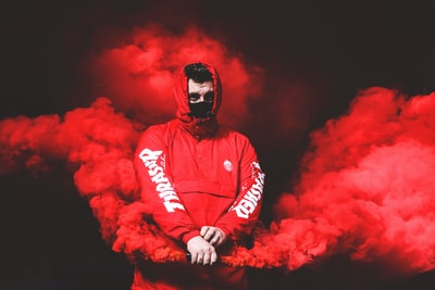 man in red thrasher pullover hooded jacket with red smoke smoke grenade teams background