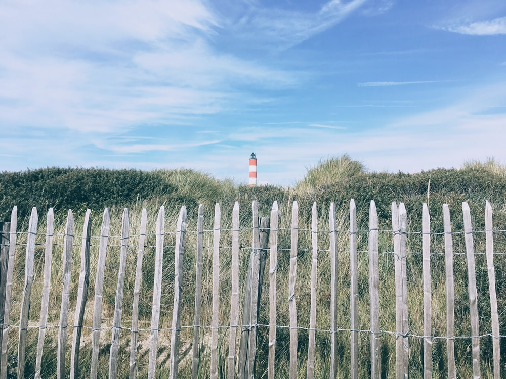 foreground photography of fence overlooking lighthouse