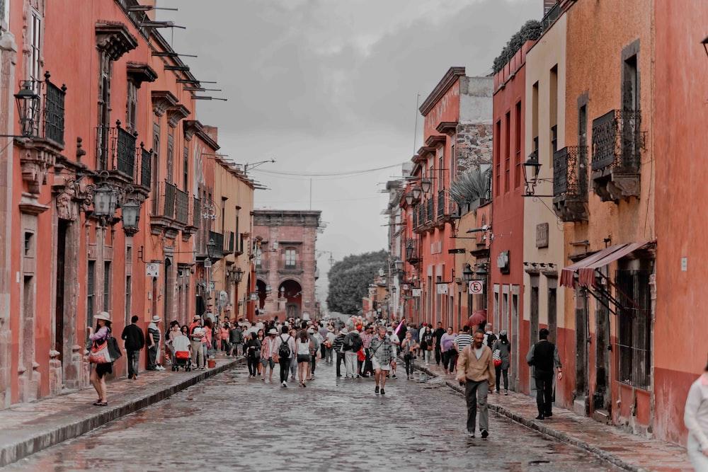 people walking between orange concrete buildings