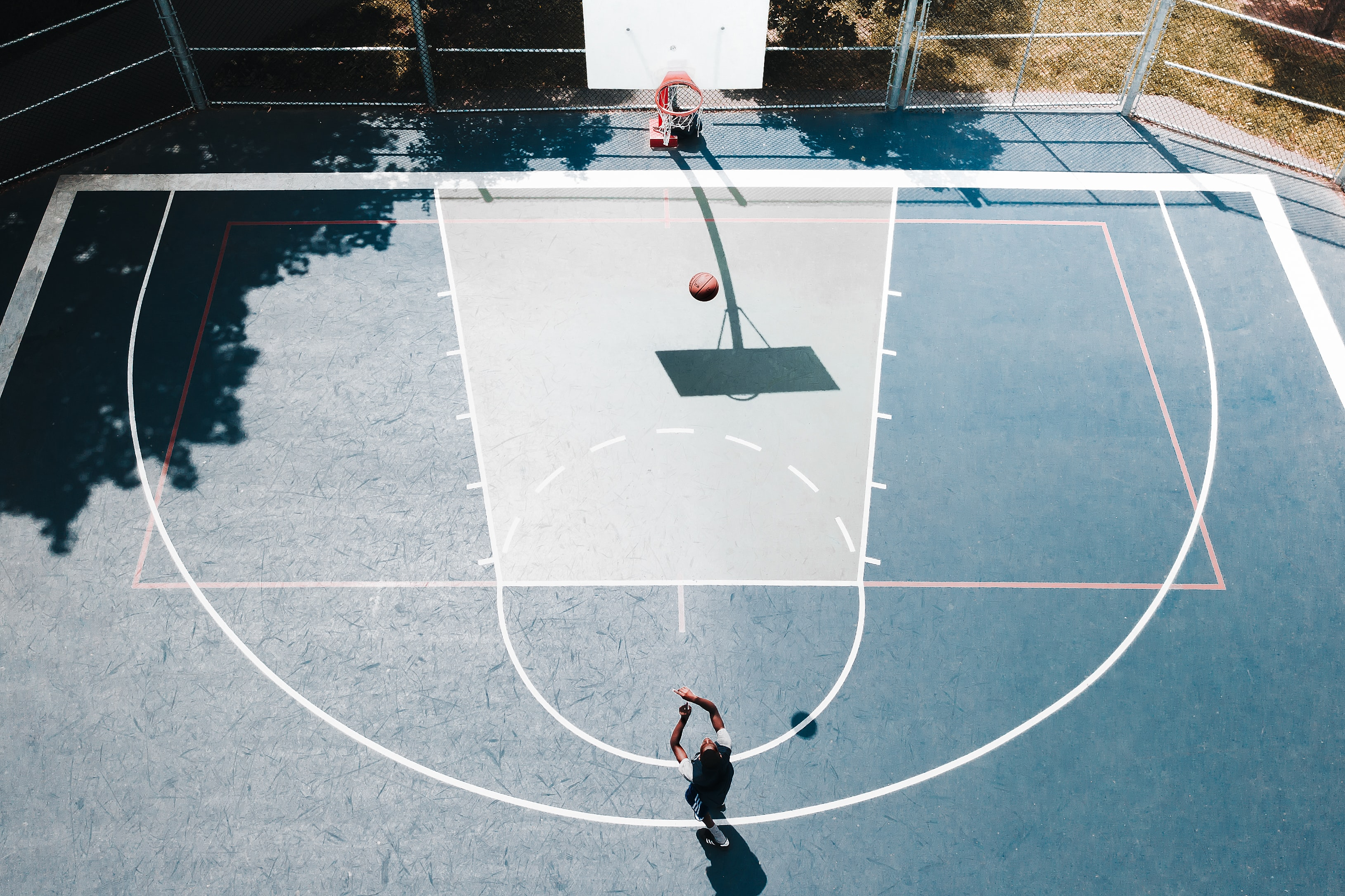 Drone view of person shooting basketball into hoop on a court outdoors
