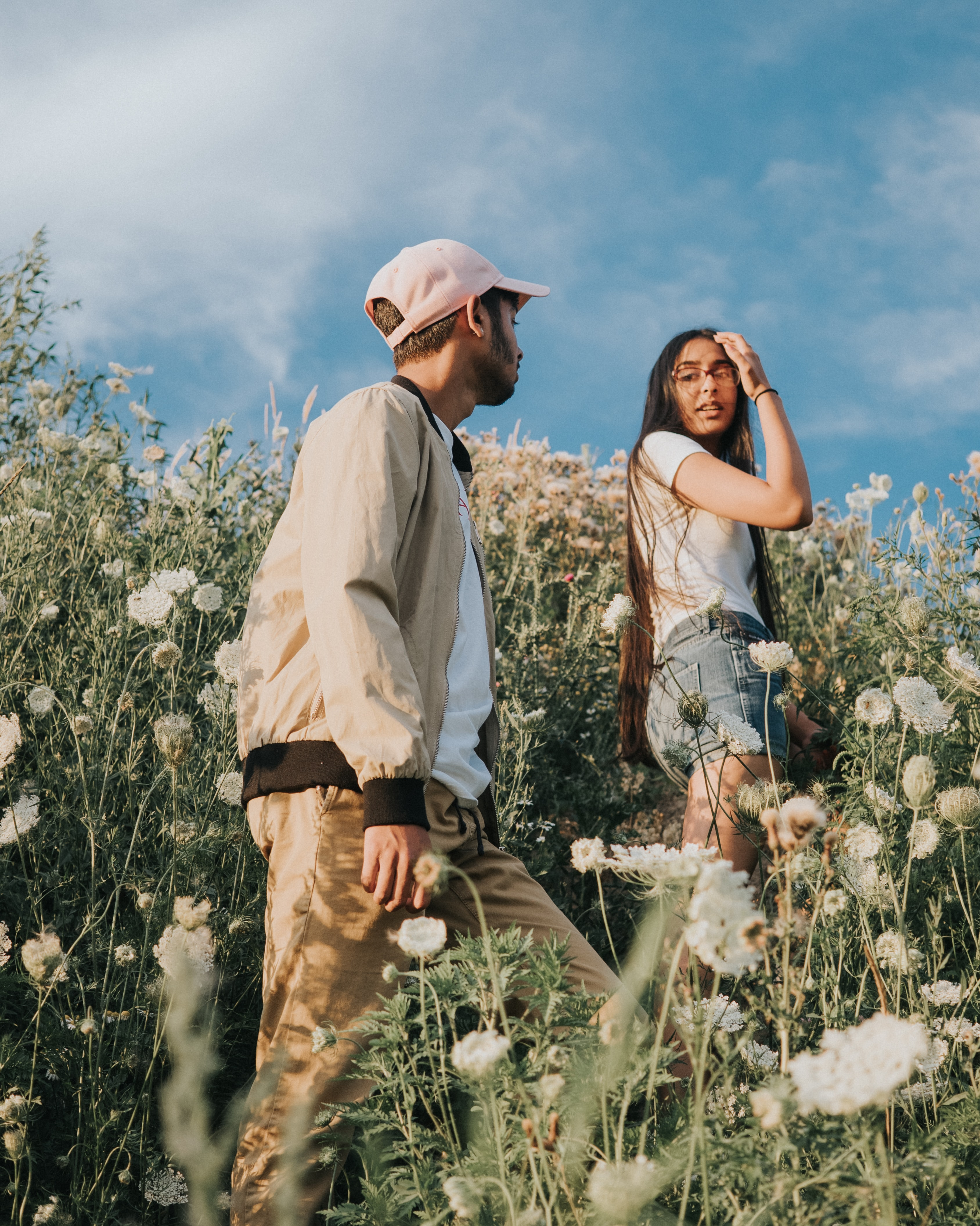 A guy and a girl walking through a flowery meadow