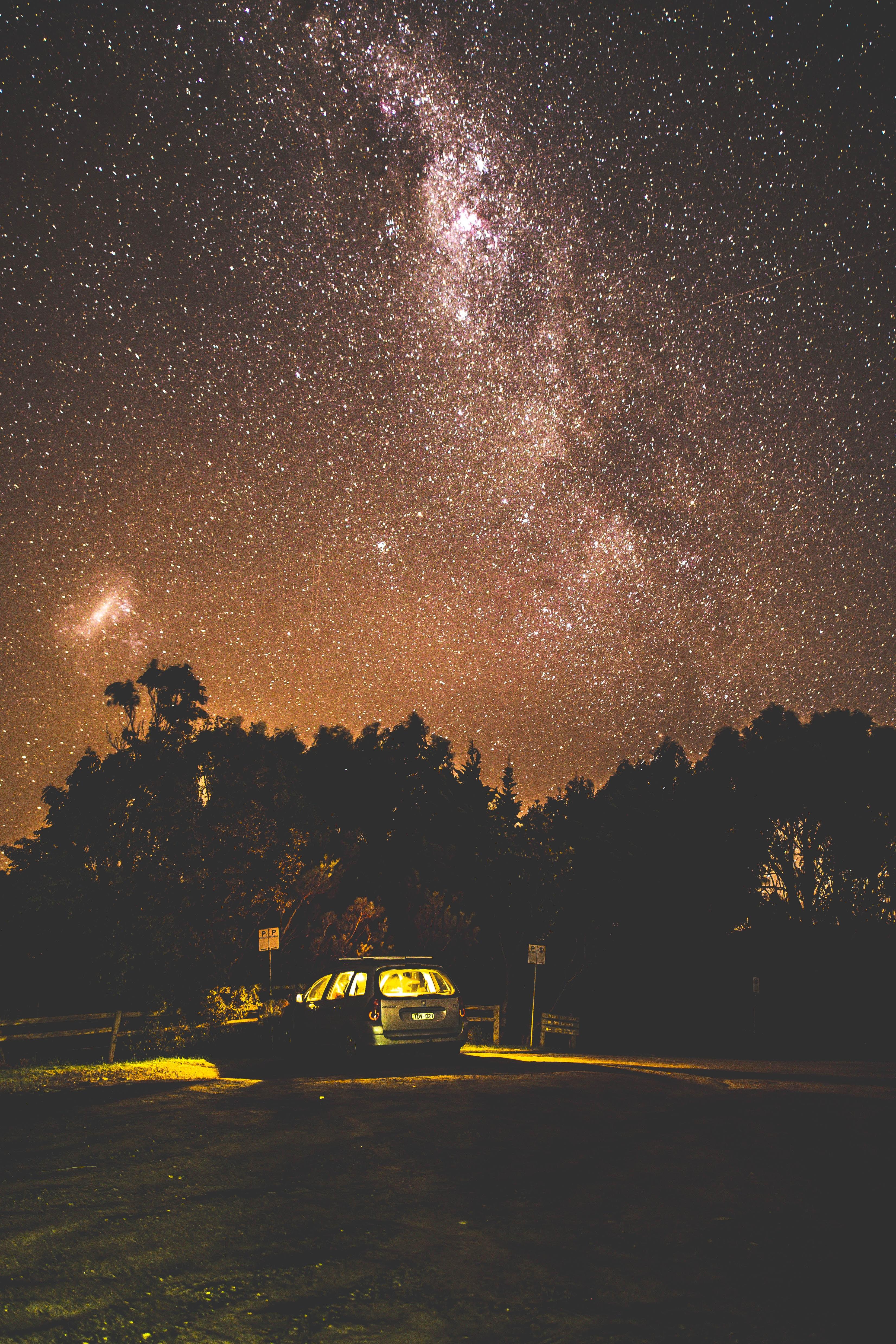 Lights inside a car parked near a forest under a starry evening sky