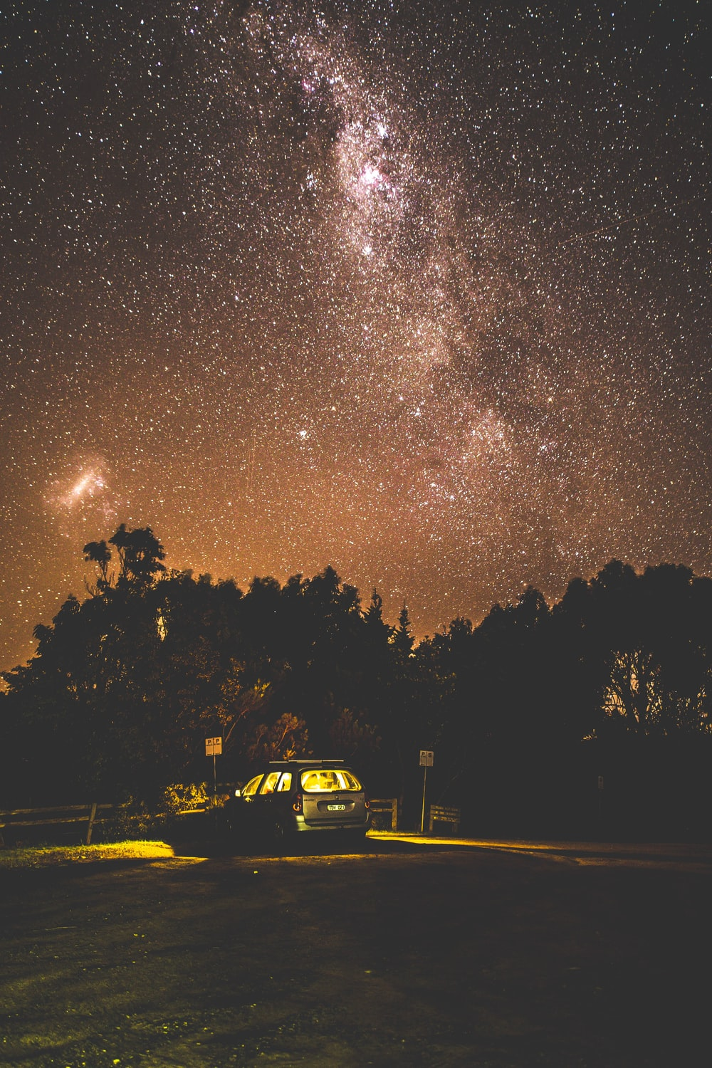 milky way over silhouette trees and car