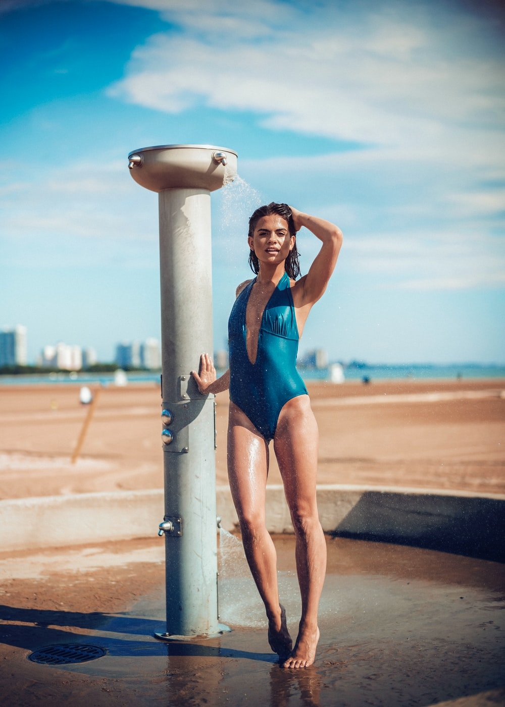Woman in a one piece swimsuit showering at the beach after a swim
