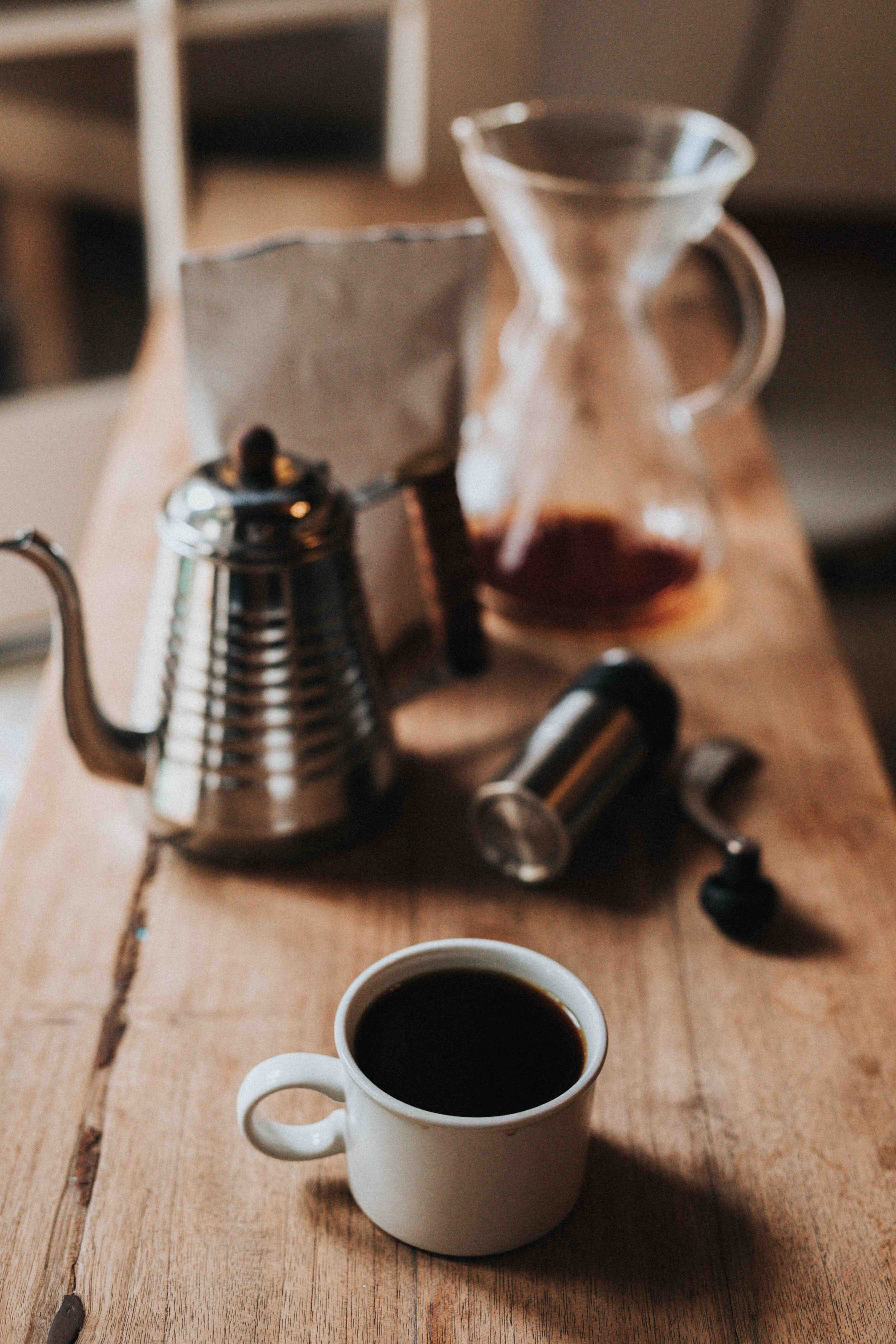 shallow focus photography of white coffee mug with black coffee on table