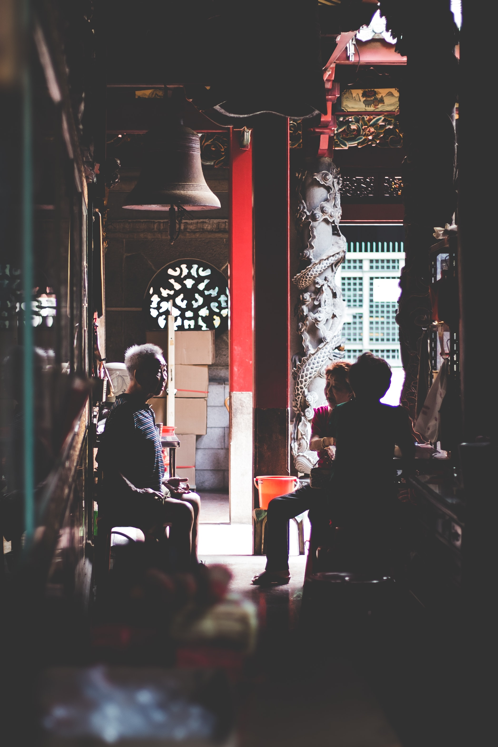 low-light photography of three people sitting on chairs indoors
