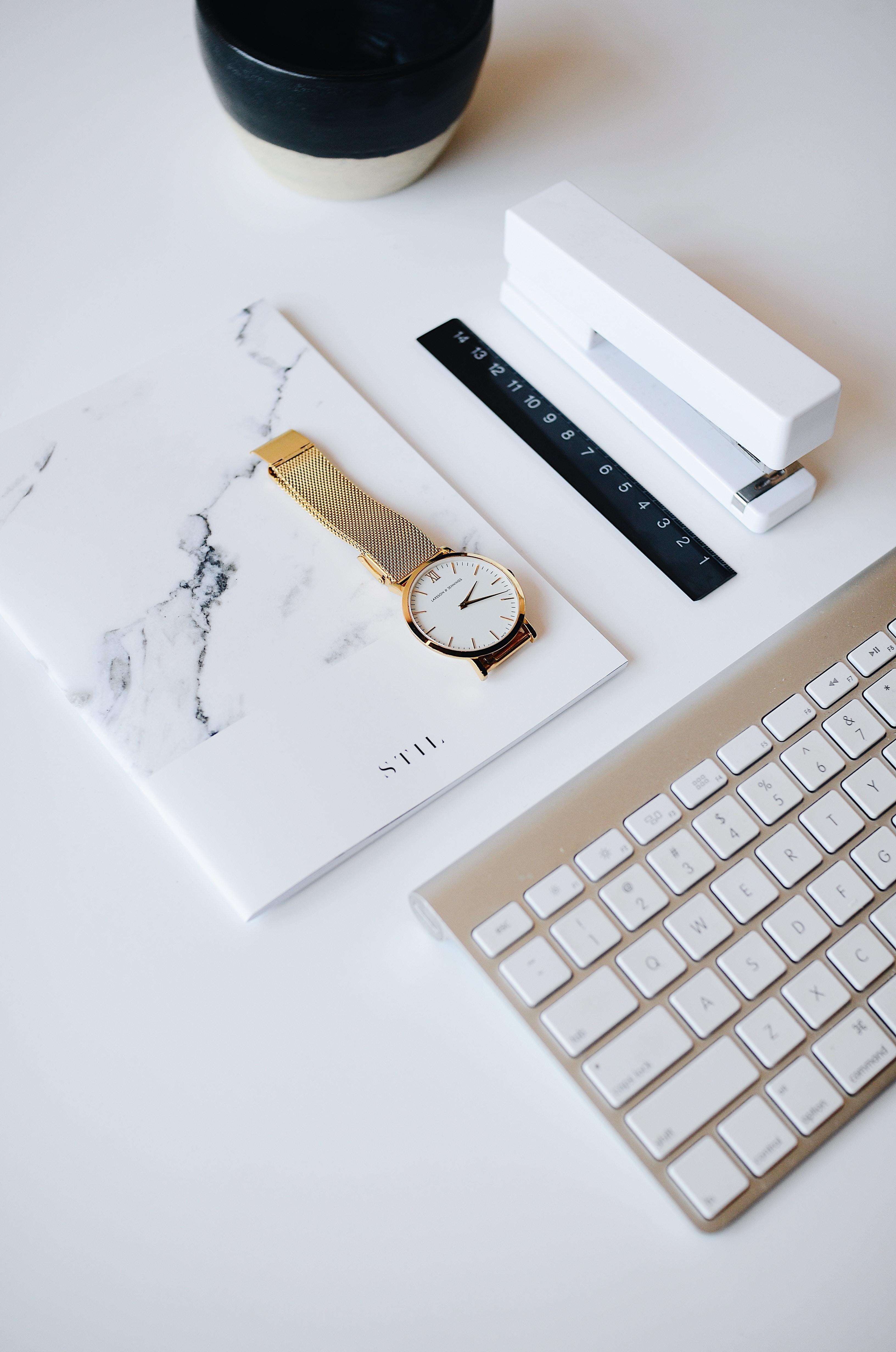 watch on top of book beside stapler near Apple keyboard
