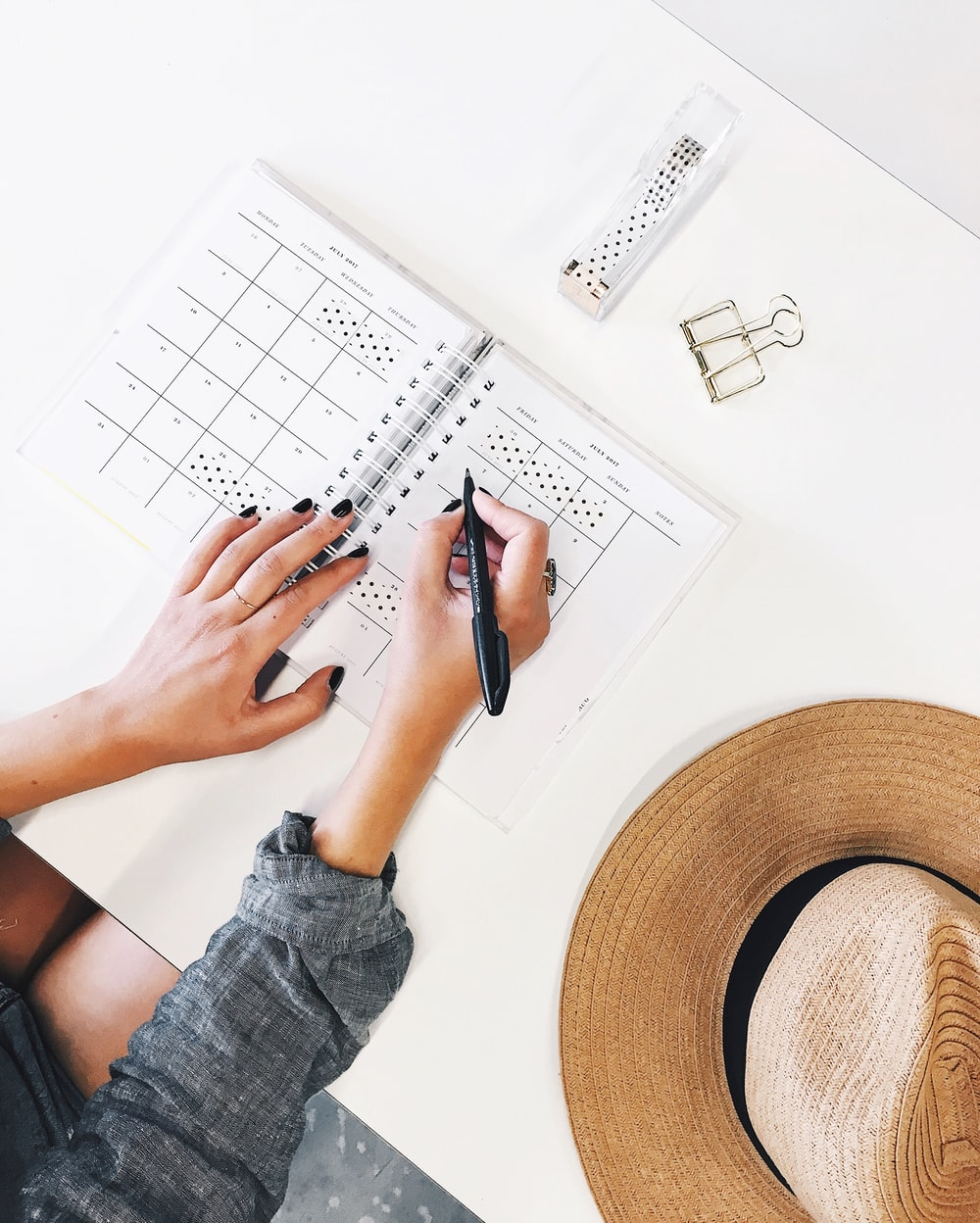 Photo Via: https://unsplash.com/photos/-837JygbCJo, An overhead shot of a person writing in a planner on a desk