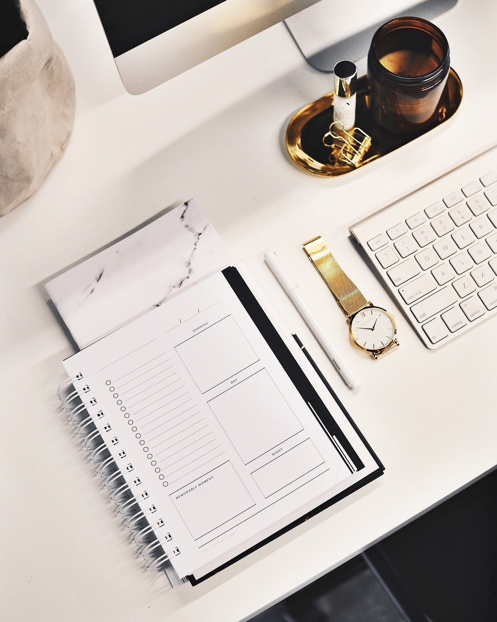 A flatlay image of a desk with a keyboard, gold watch, notebook and more.