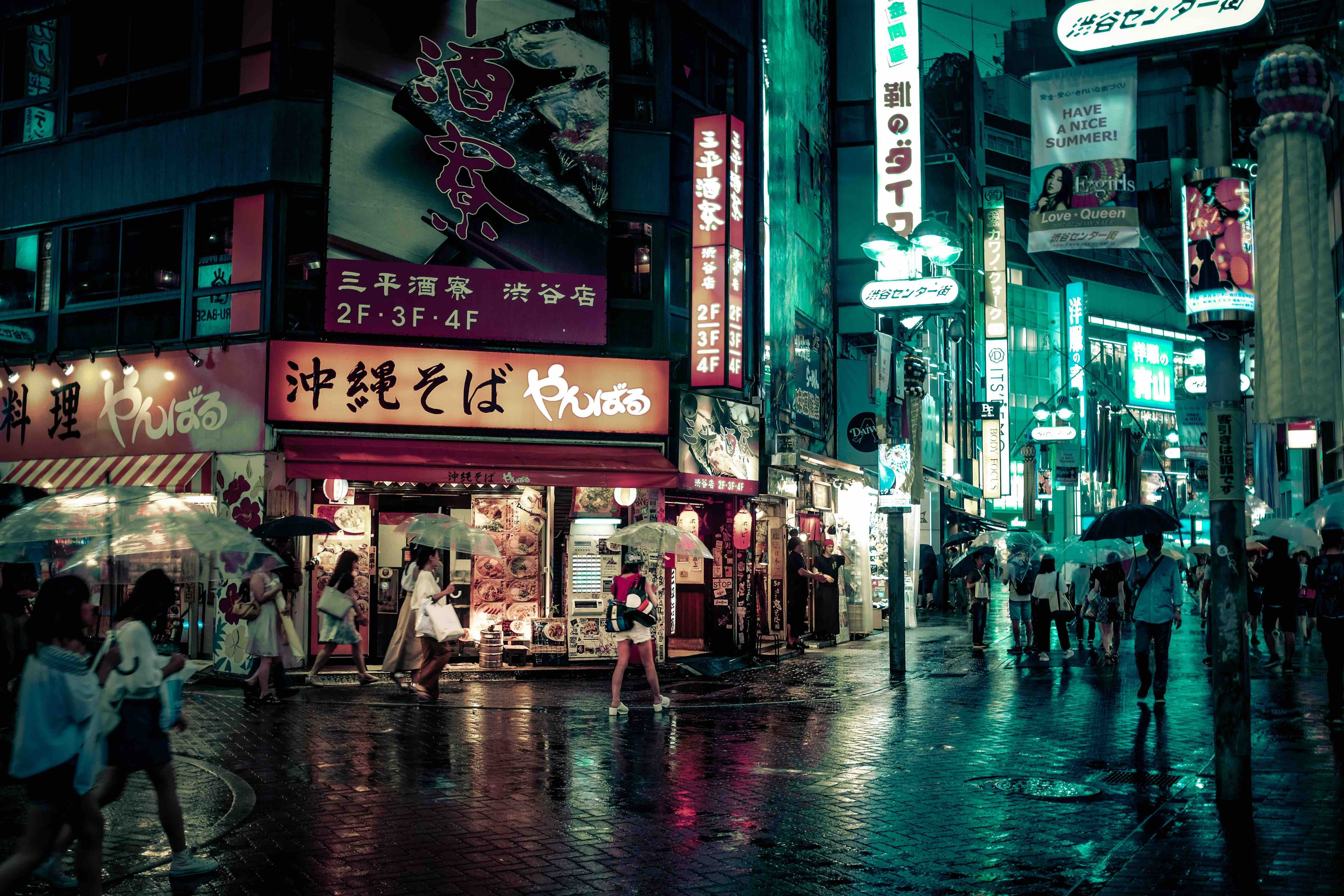 People with umbrellas in a busy street in Tokyo at night