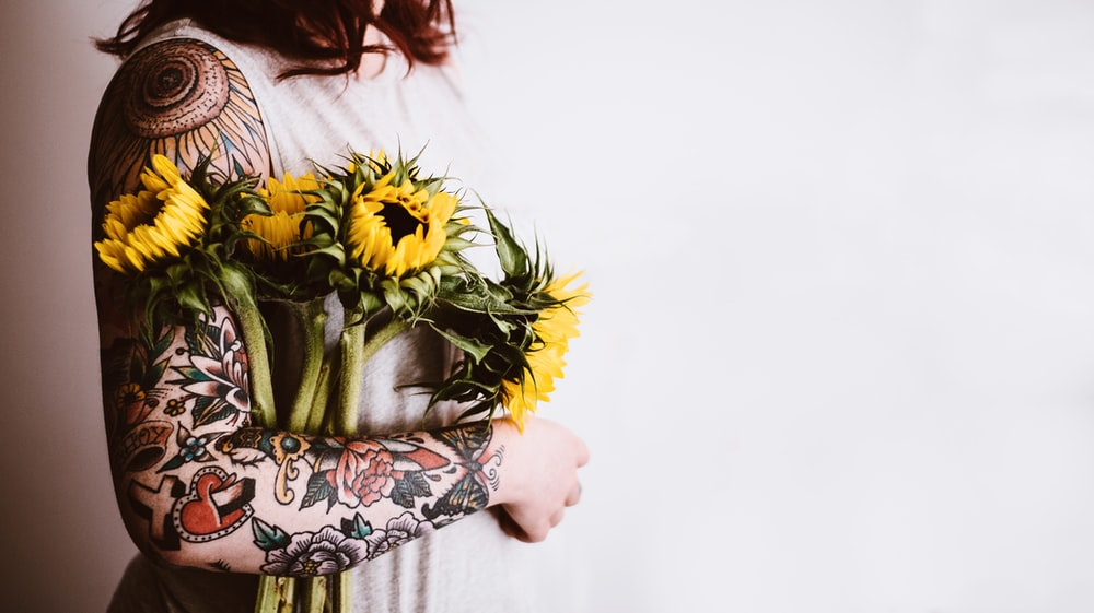 woman holding yellow sunflowers on her right arm