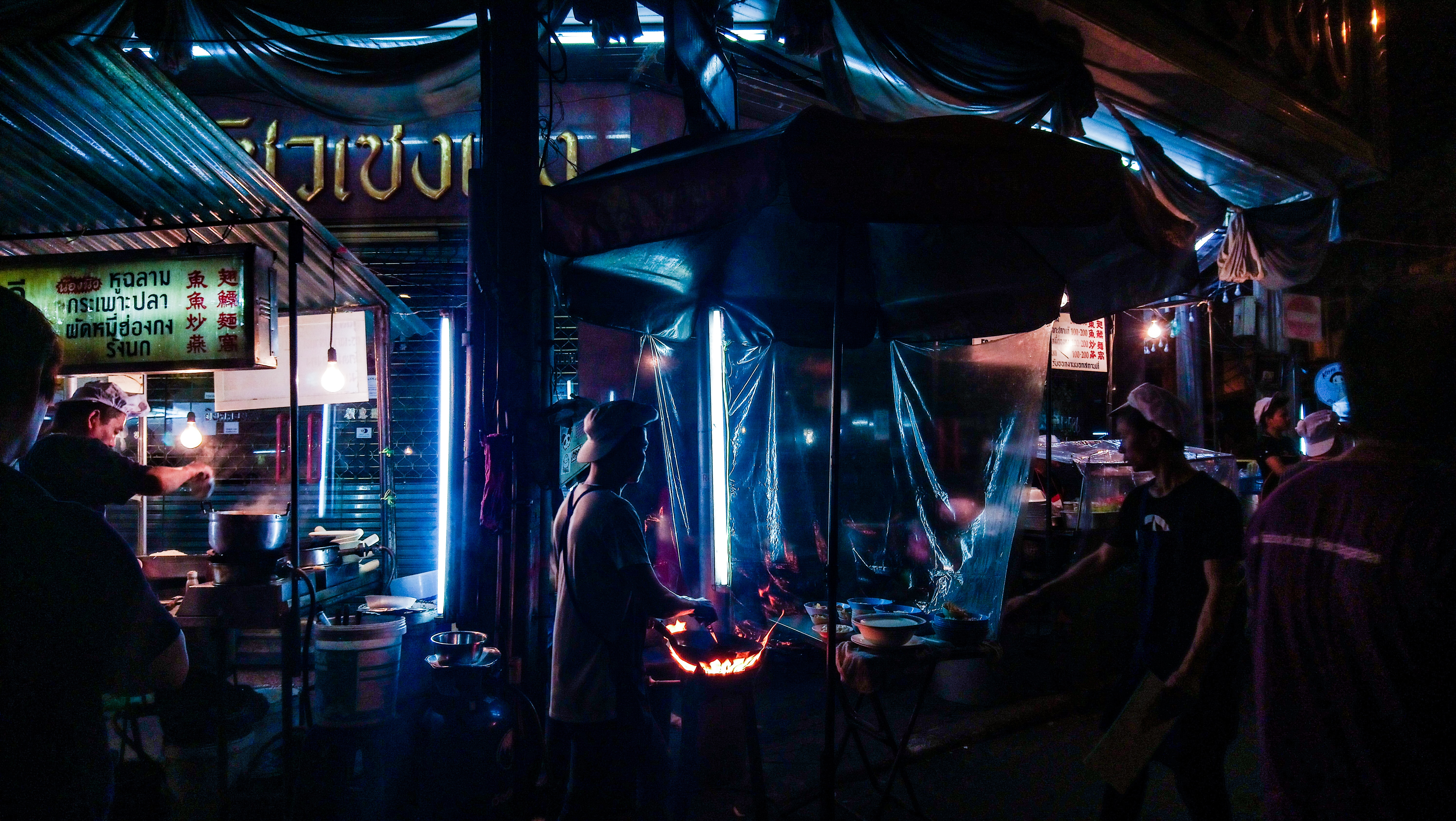 man grilling meat while man in black shirt standing in front of food stall
