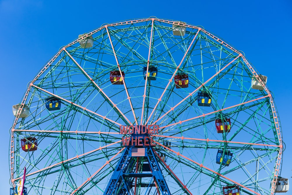 pink and white ferris wheel under blue sky at daytime