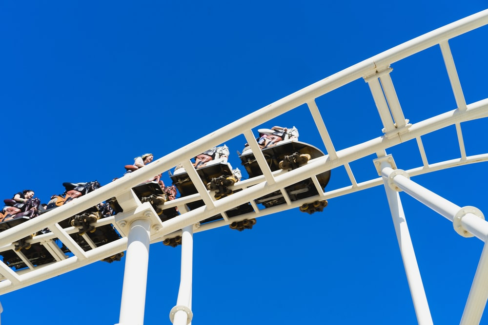 low-angle photo of people riding on roller coaster