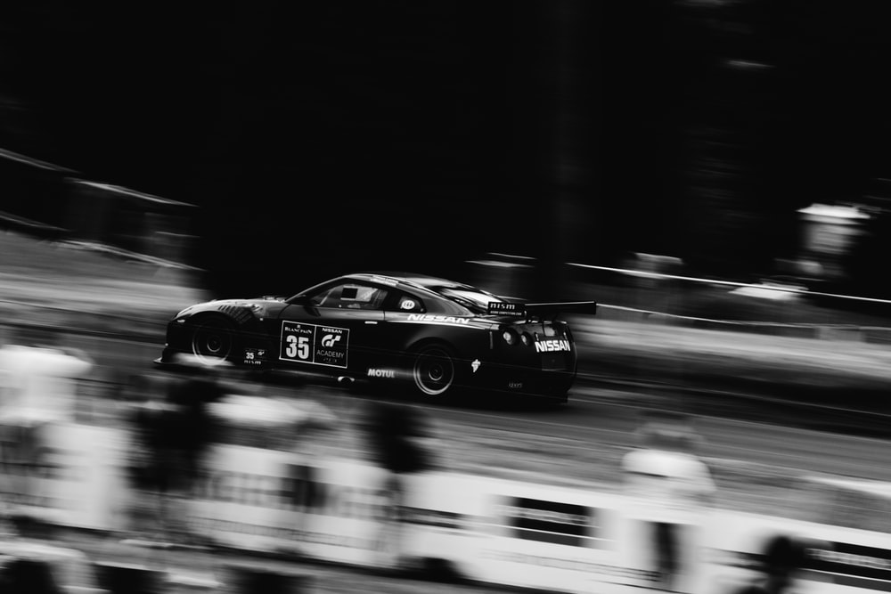 sports car in motion grayscale photography