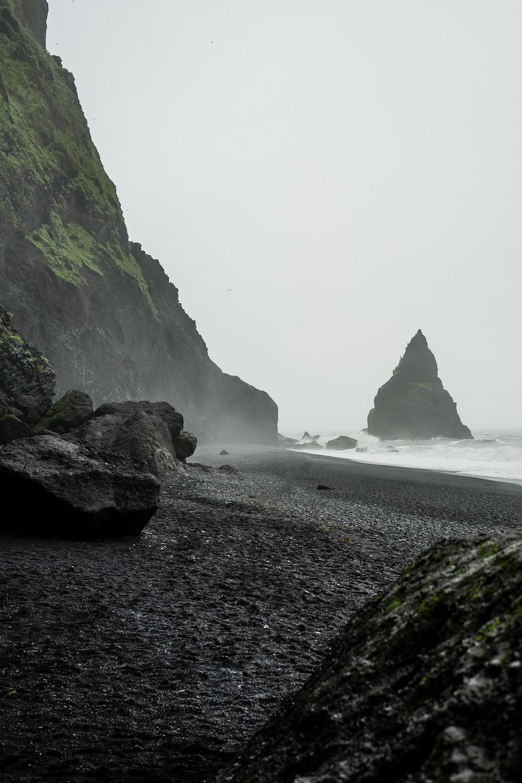 landscape photo of black rock formation on body of water near seashore