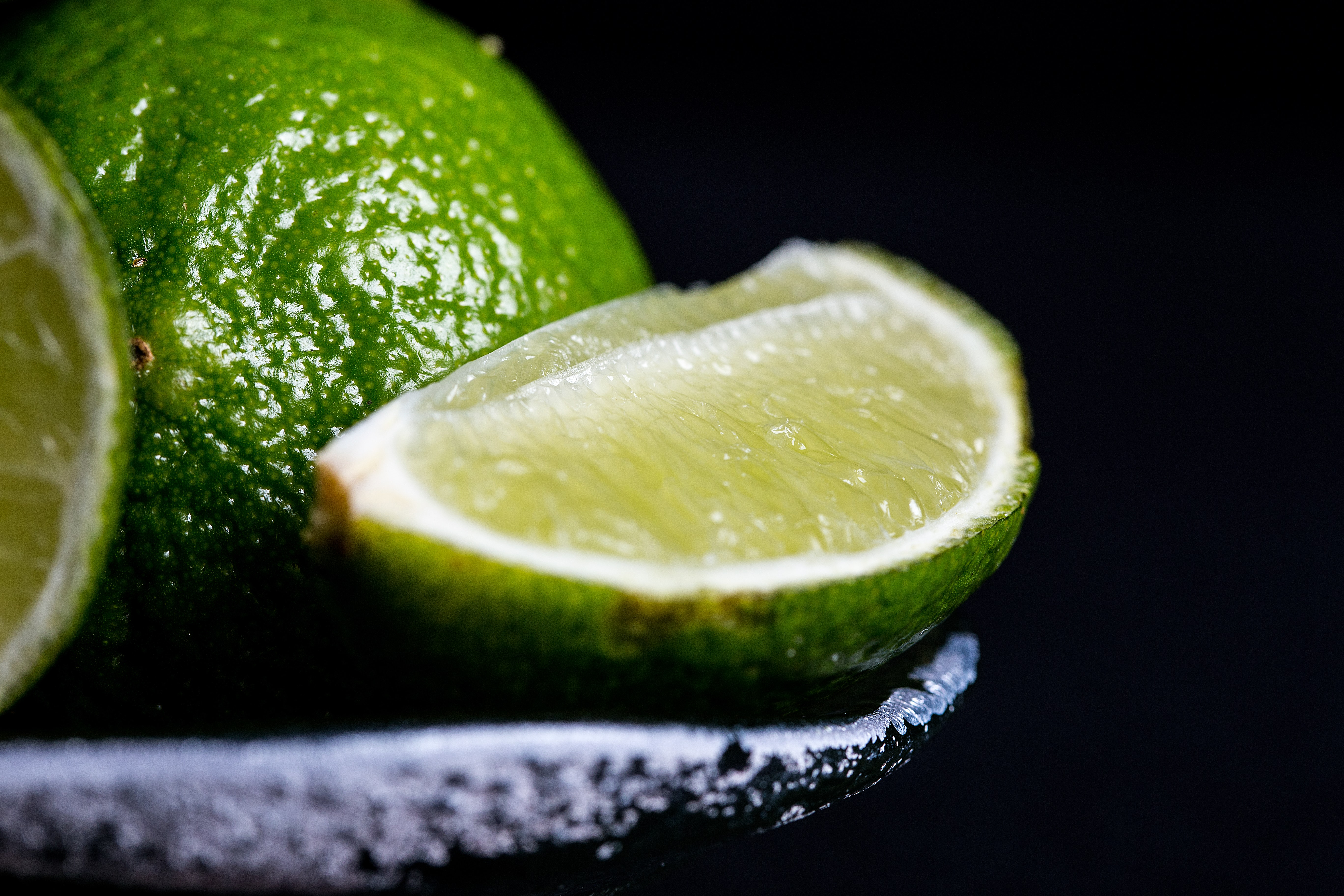 Slices of fresh lime in a bowl on a black backdrop