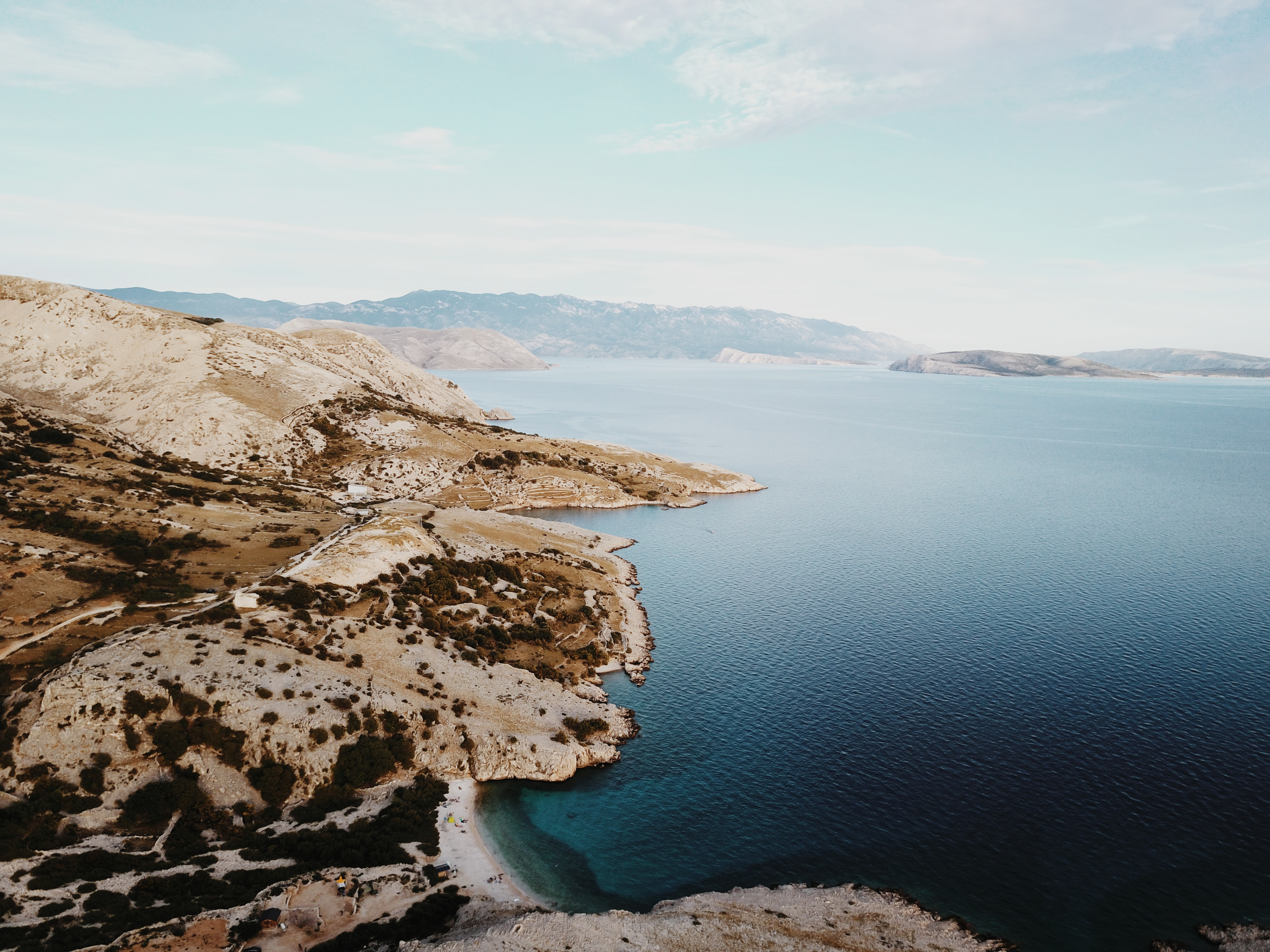Drone view of a barren shoreline by the blue ocean at Stara Baška