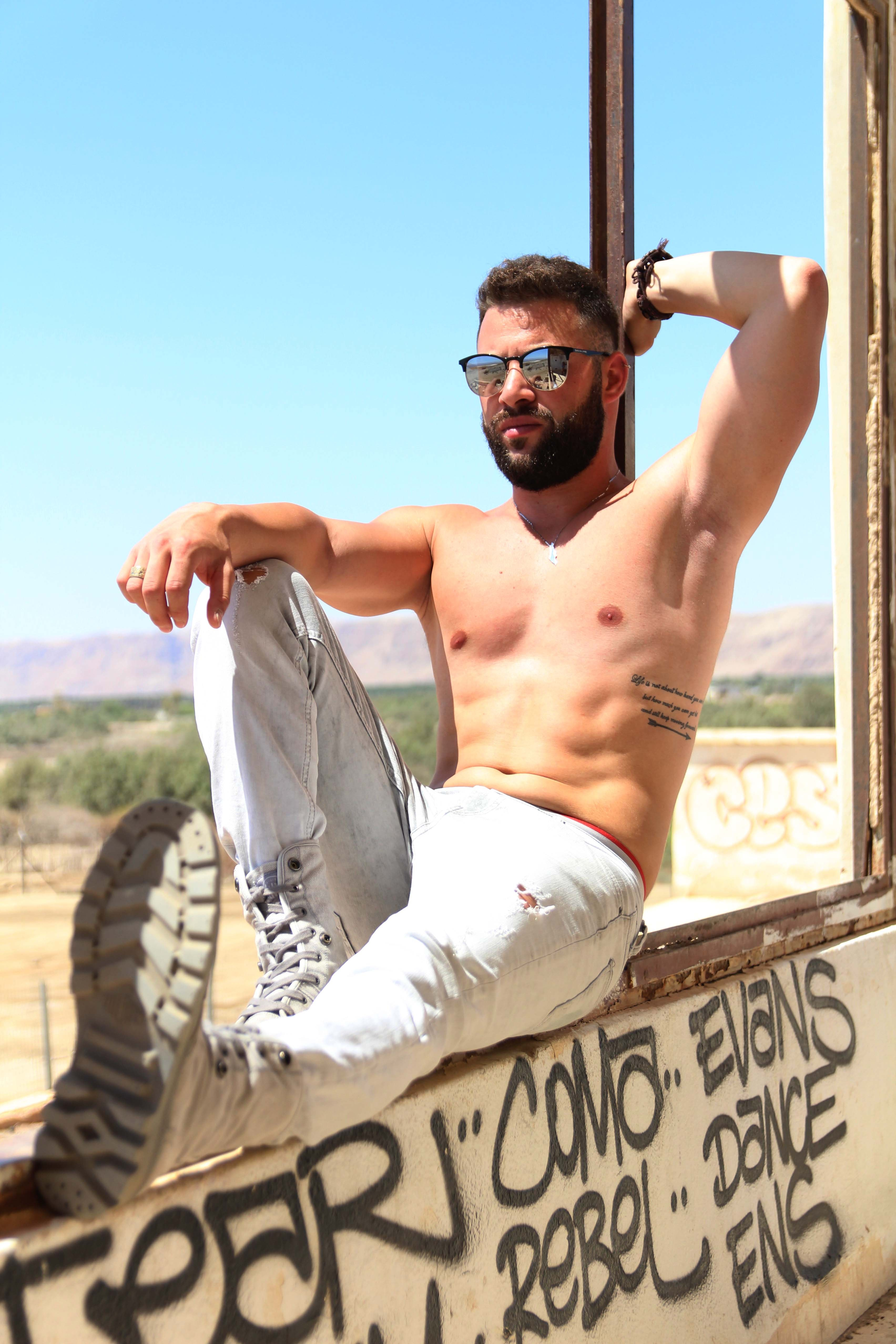 A fit shirtless man poses on a graffitied window frame outdoors by the Dead Sea