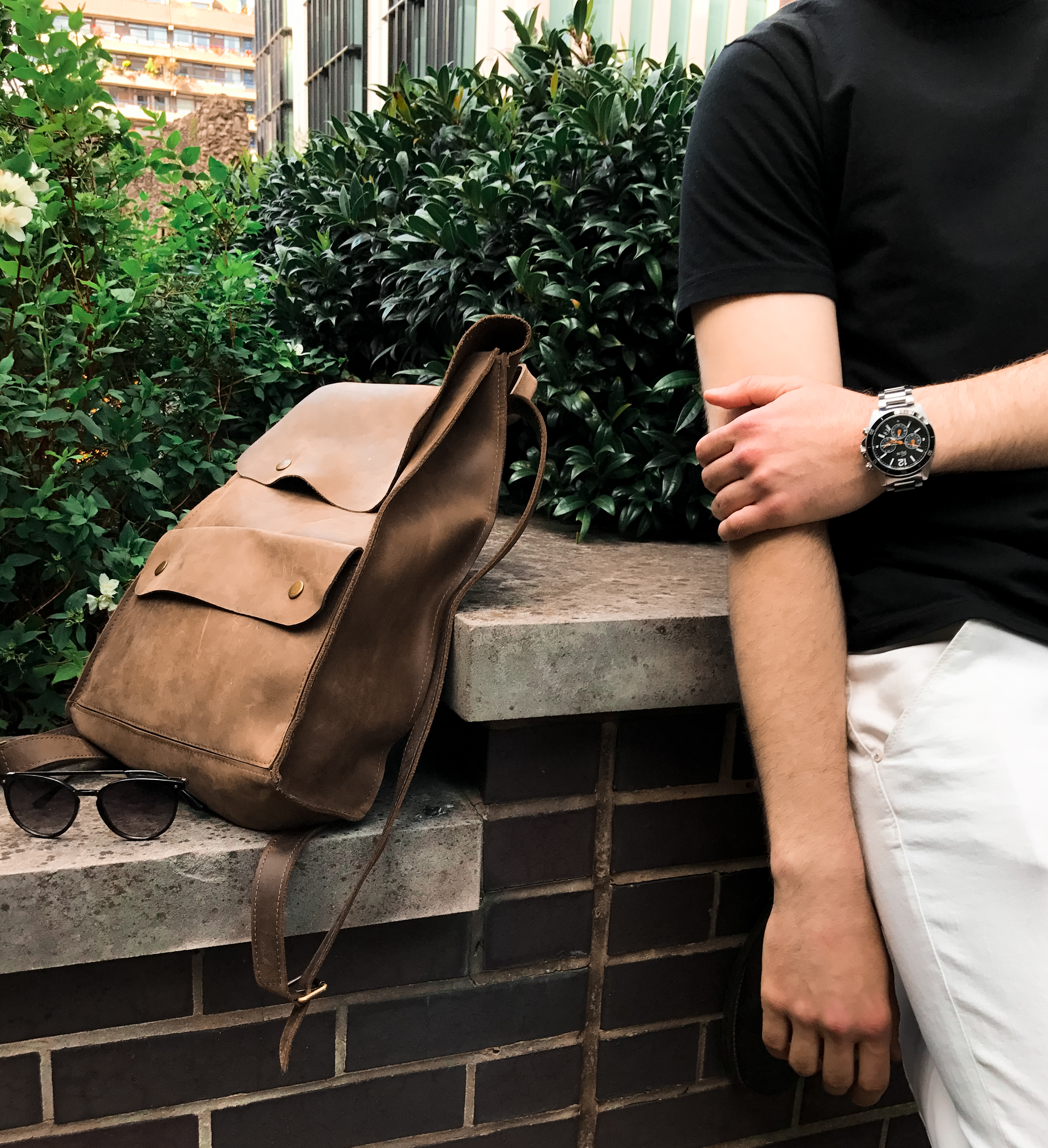 Low shot of a trendy backpack, sunglasses, and a person wearing a watch