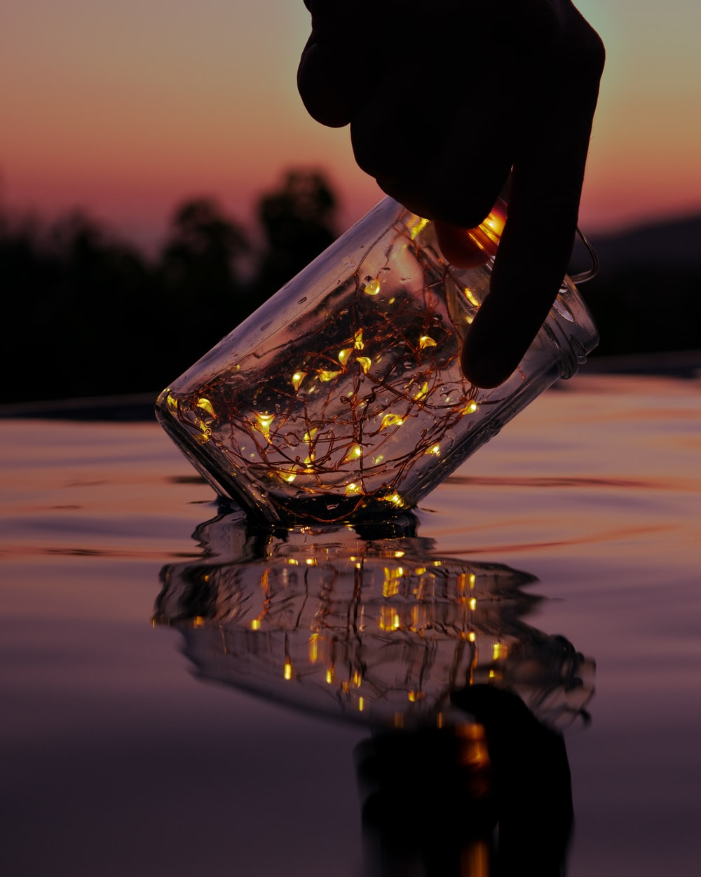 person holding string lights on clear glass jar above body of water