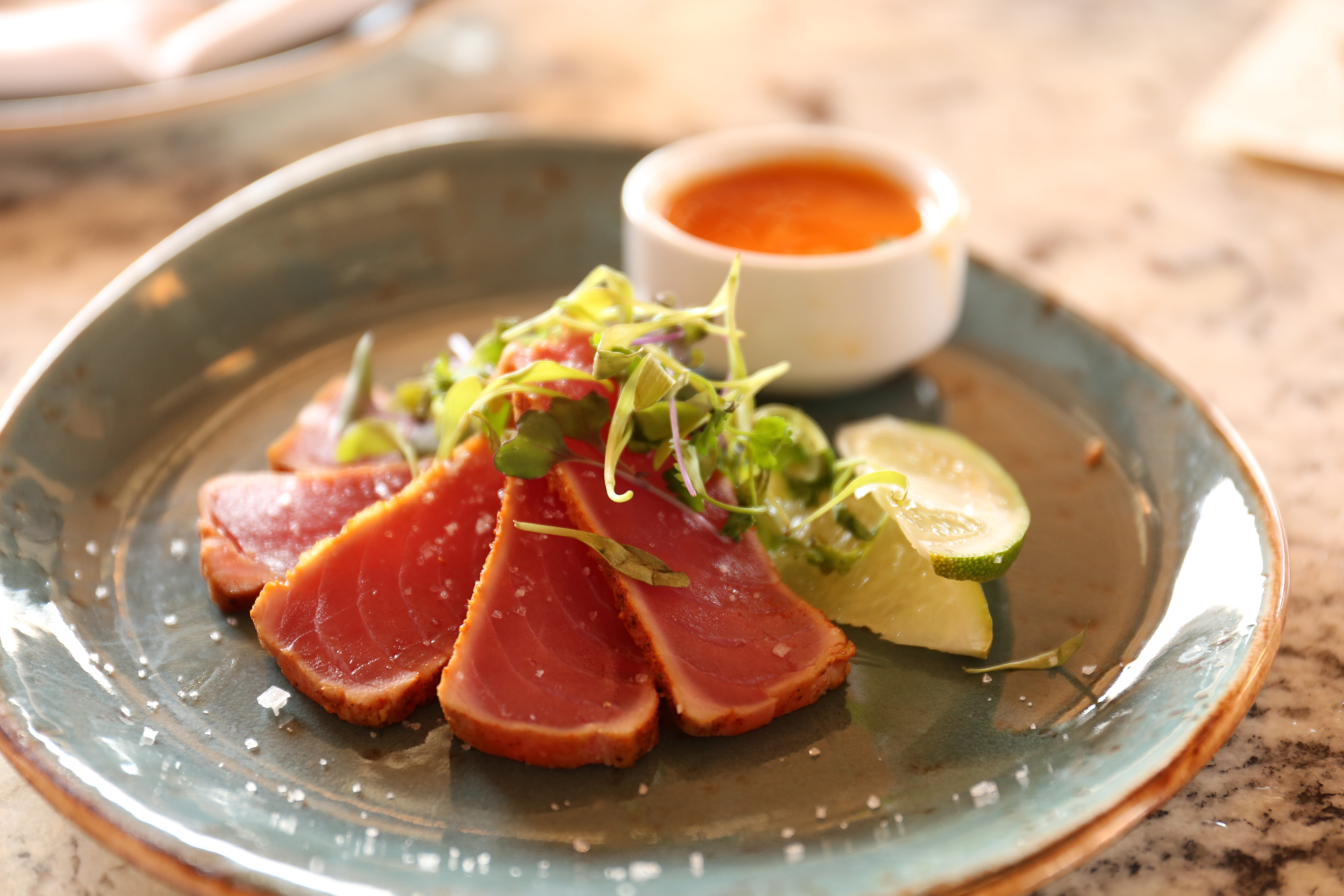 A saucer of sliced raw fish garnished with herbs and lime served with an orange dipping sauce
