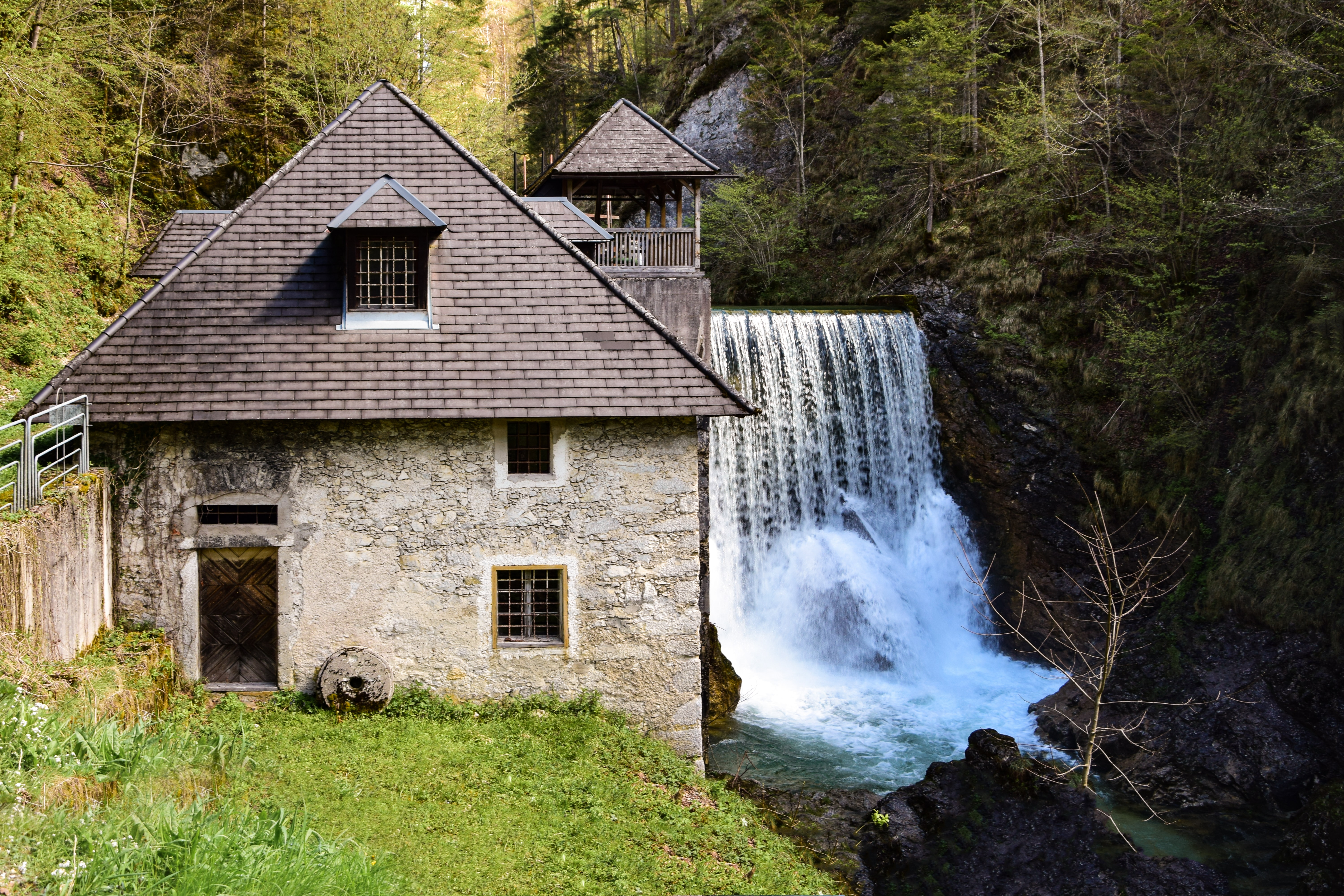 An old building next to a small waterfall in a forest