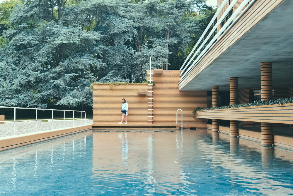 woman wearing white shirt standing beside brown bricked wall and blue water pool near trees during daytime