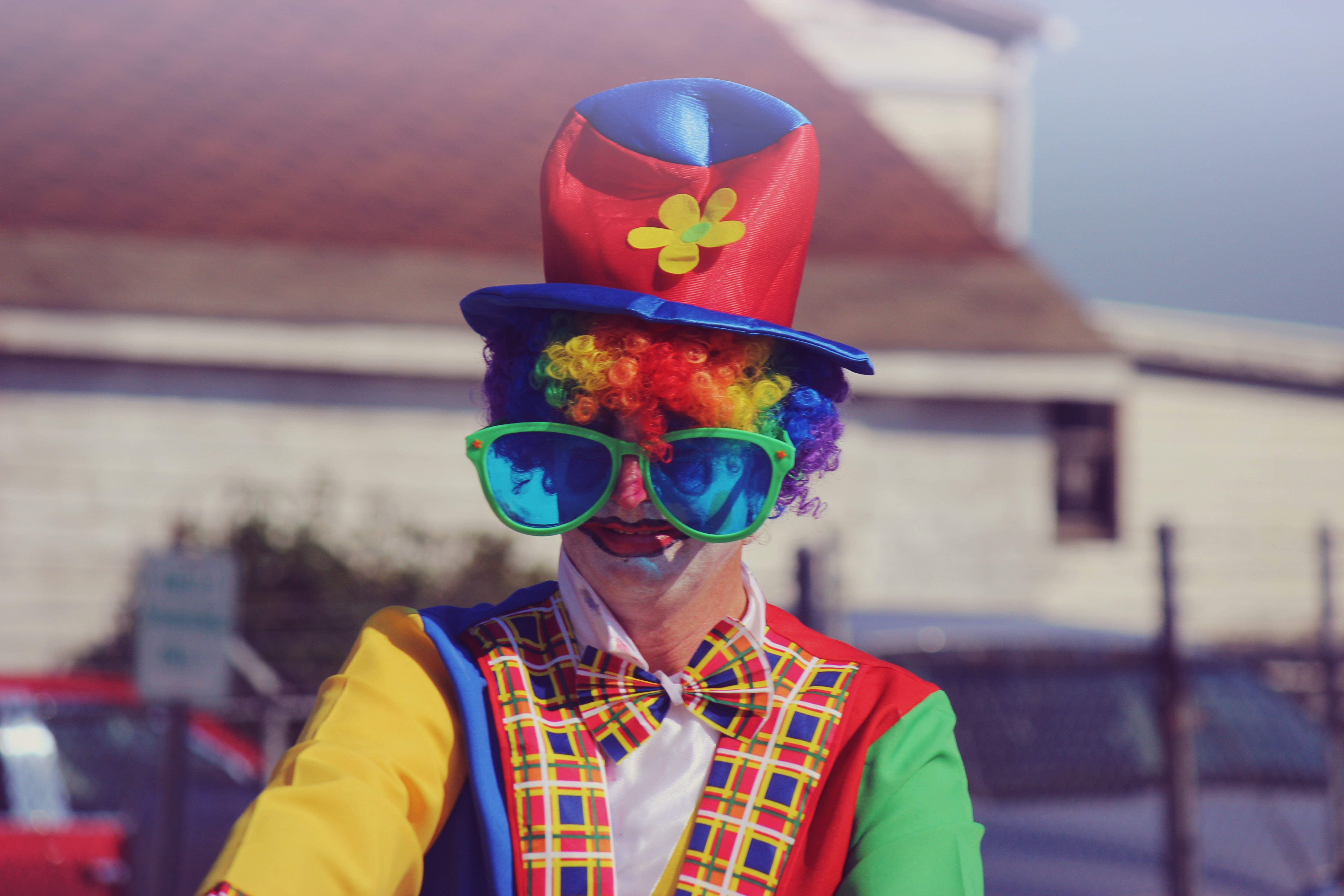 Colorful clown dressed up in a rainbow colored costume