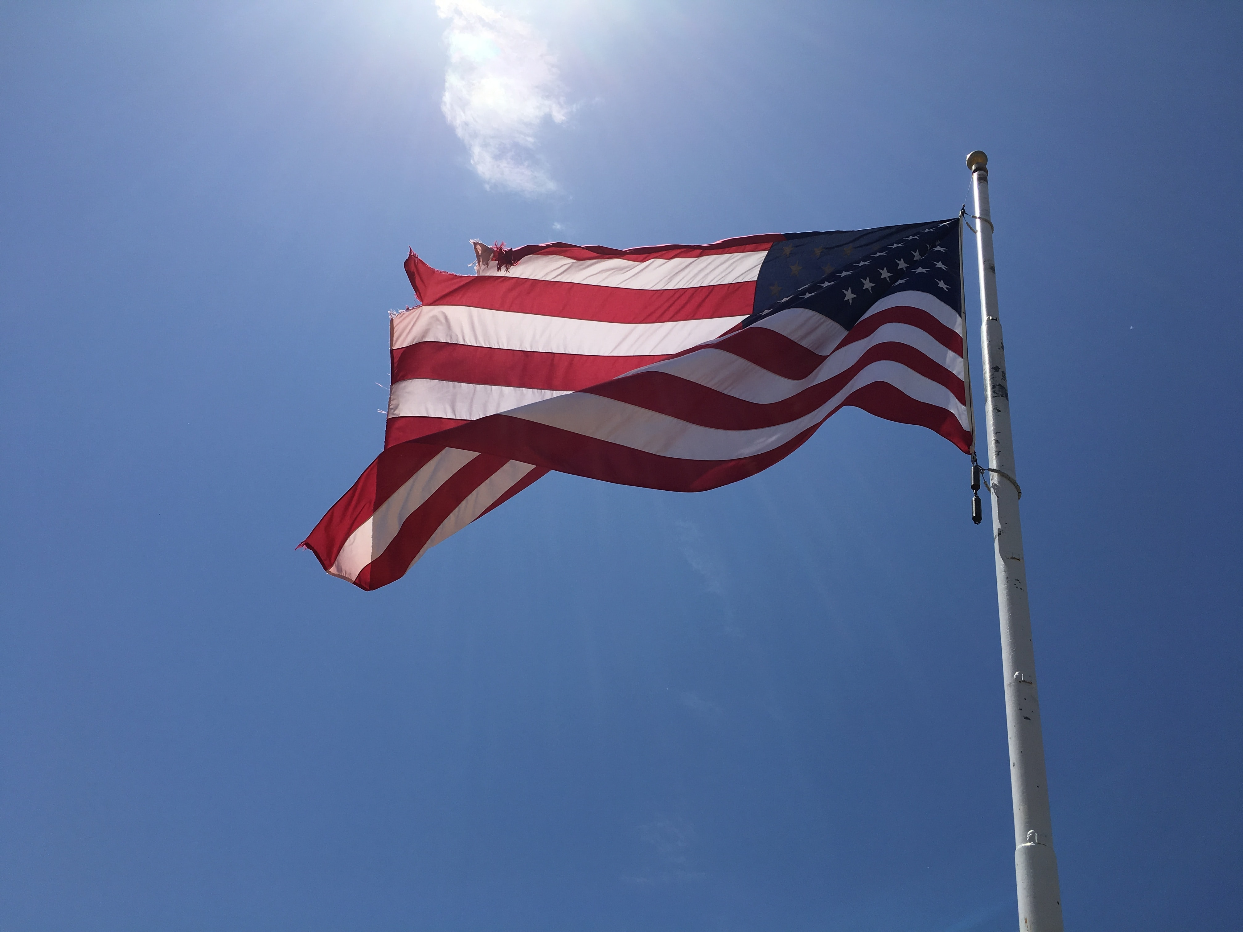 American flag flying in the wind against a sunny blue sky