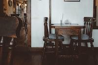 brown wooden 3-piece bistro set near white wall inside room