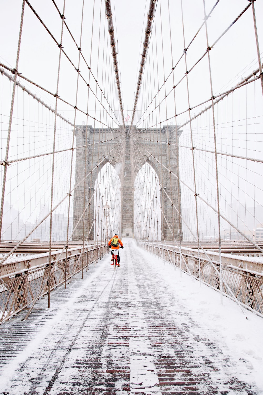 person on red bicycle running on brown bridge covered by snow