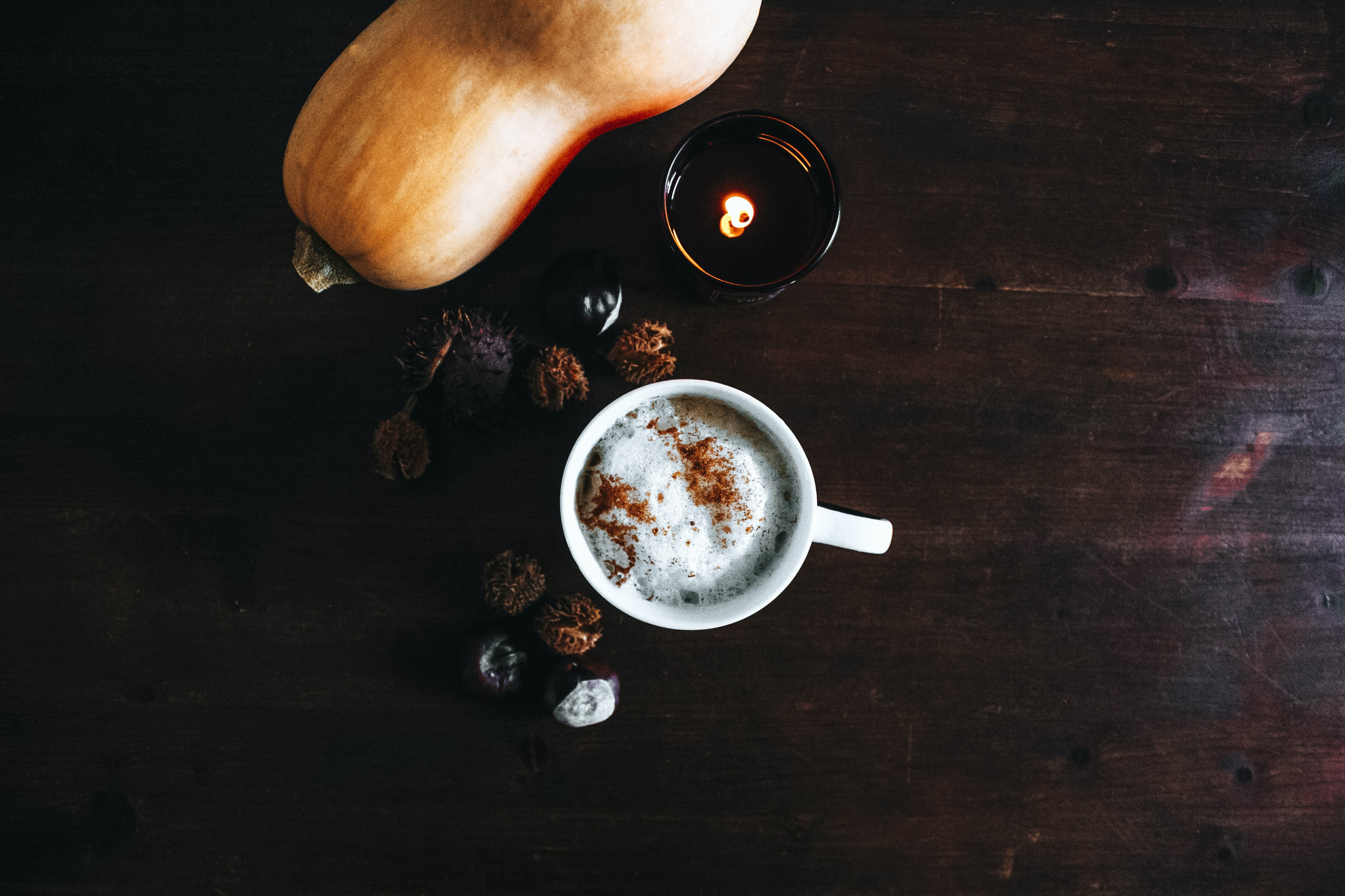A mug of coffee spiced with cinnamon beside a squash and a candle