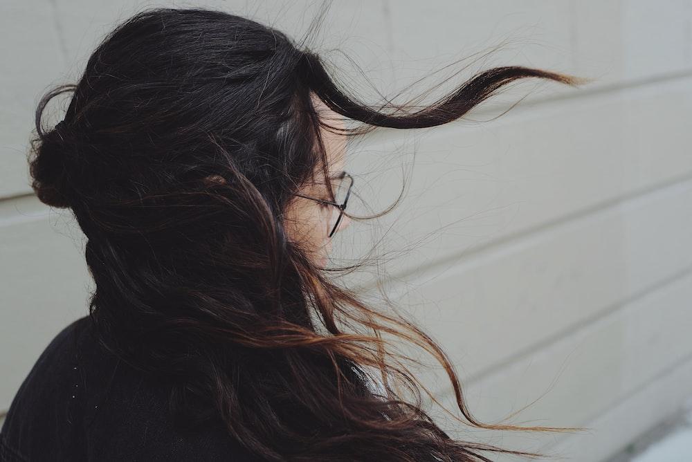 woman near white wall getting her hair blown
