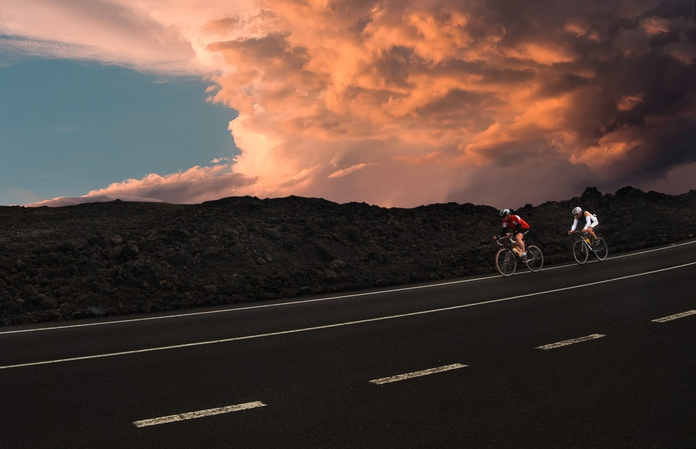 two cyclist on road during golden hour
