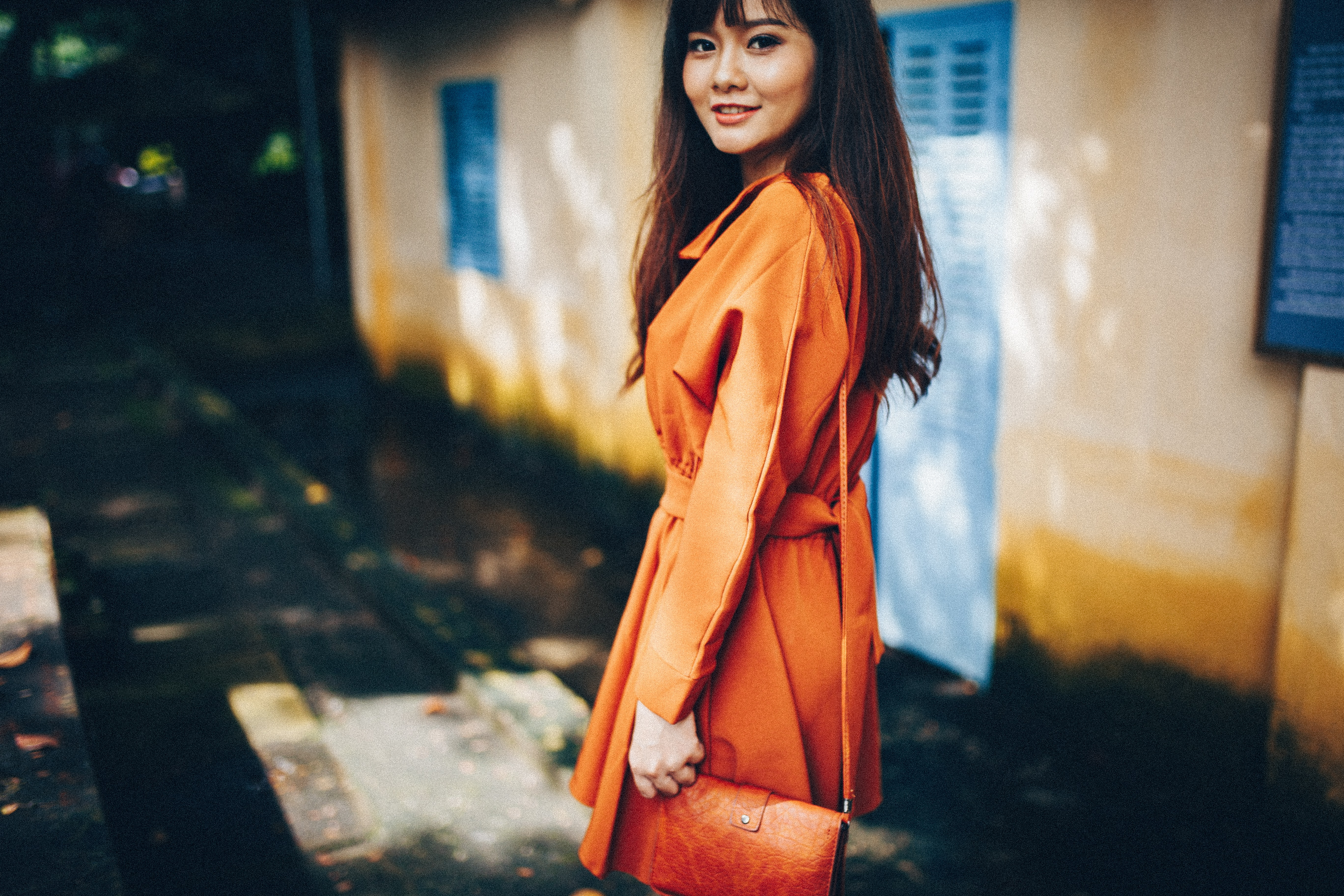 A woman in an orange coat with a purse smiles over her shoulder beside a house