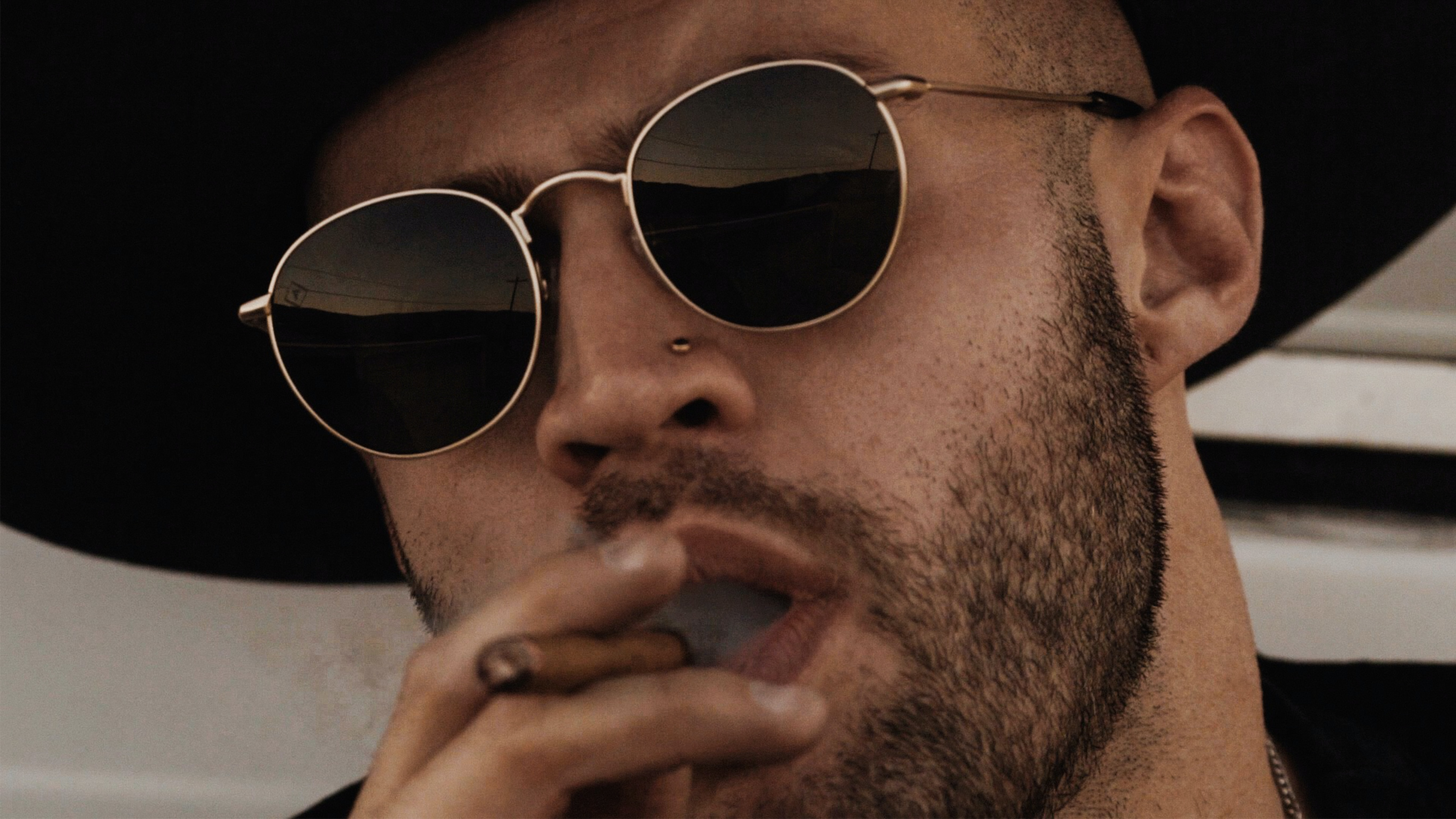 Close up of a man in a hat and sunglasses smoking a cigarello