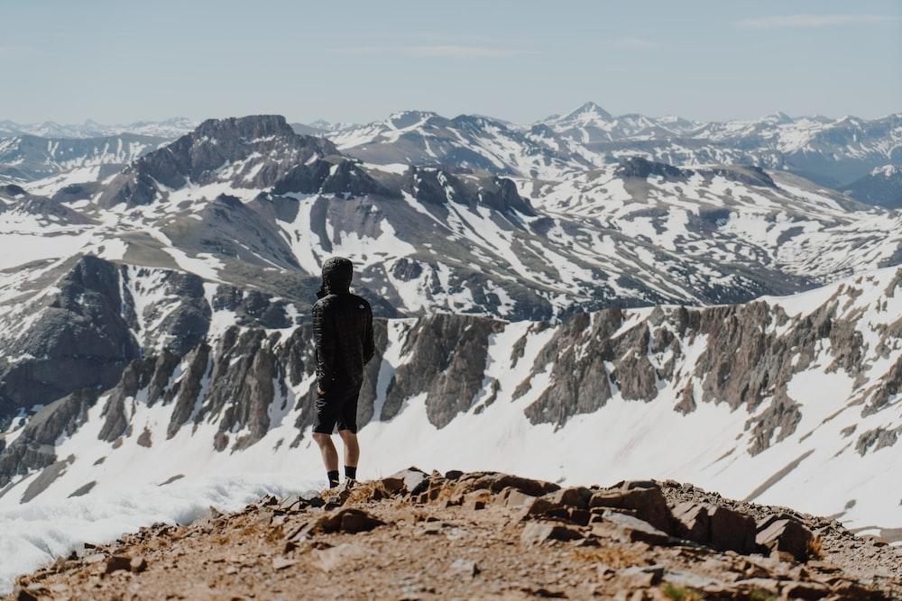man wearing black shorts standing on rock formation facing on mountain