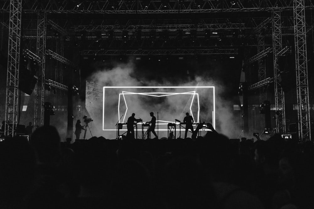 silhouette photo of rock band on stage performing in front of audience