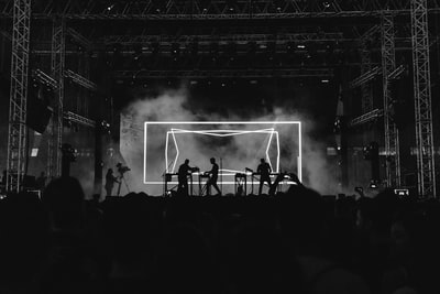 Black and white shot of band playing on stage with neon backdrop and crowd in Athens