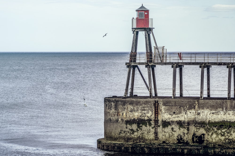 red and grey lighthouse near body of water during daytime
