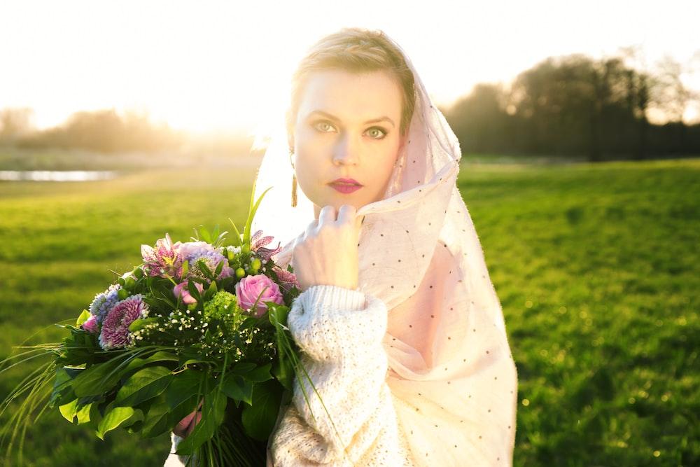 woman wearing pink veil holding pink flower bouquet