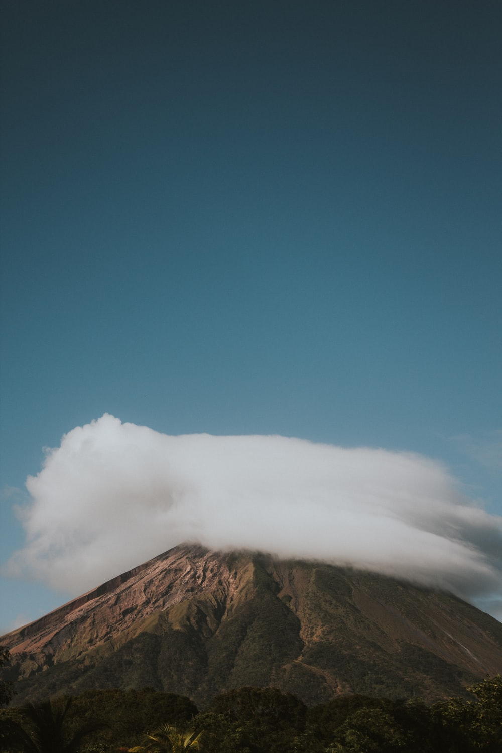 clouds above mountain under clear blue sky