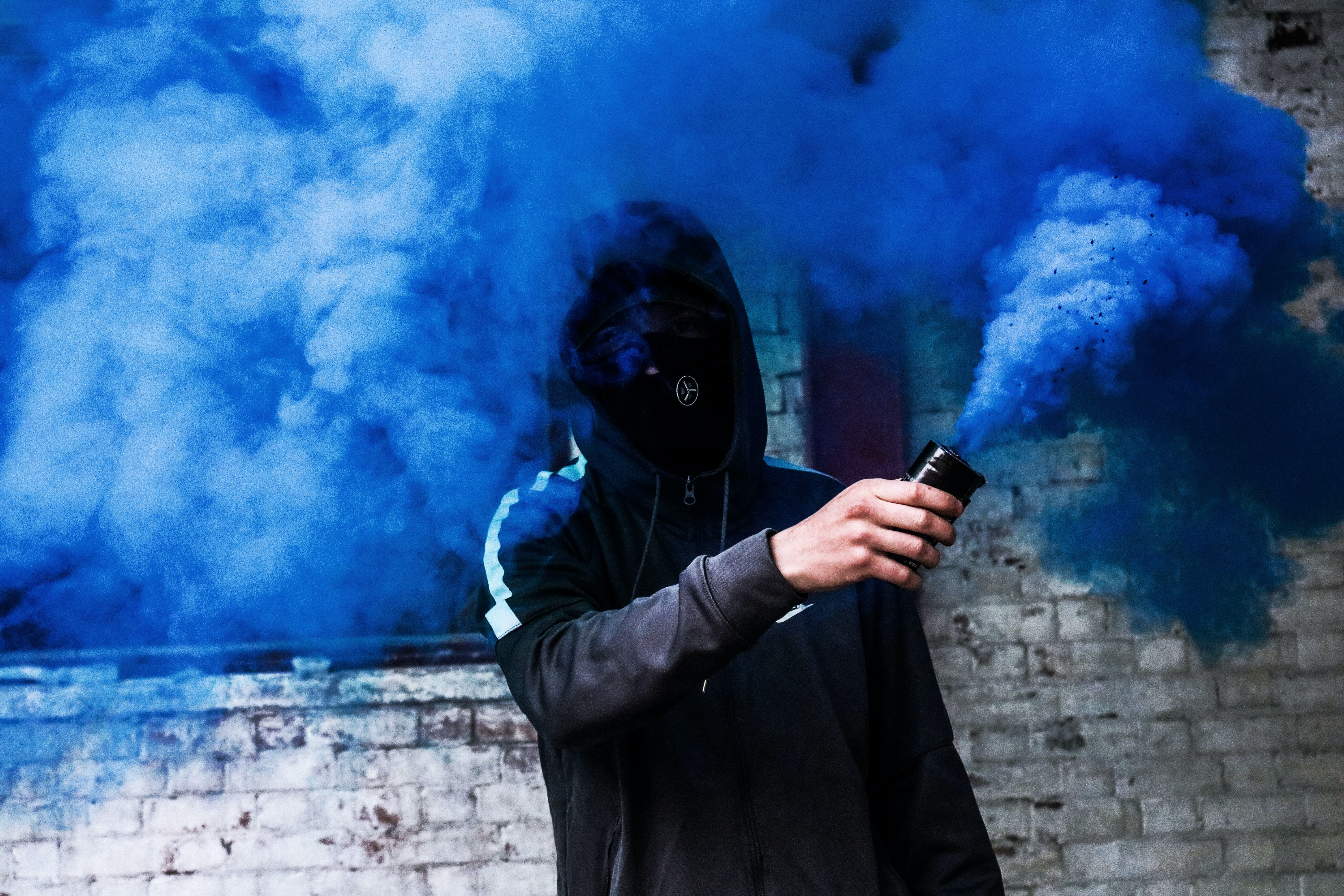 person covered with mask and hoodie using blue smoke