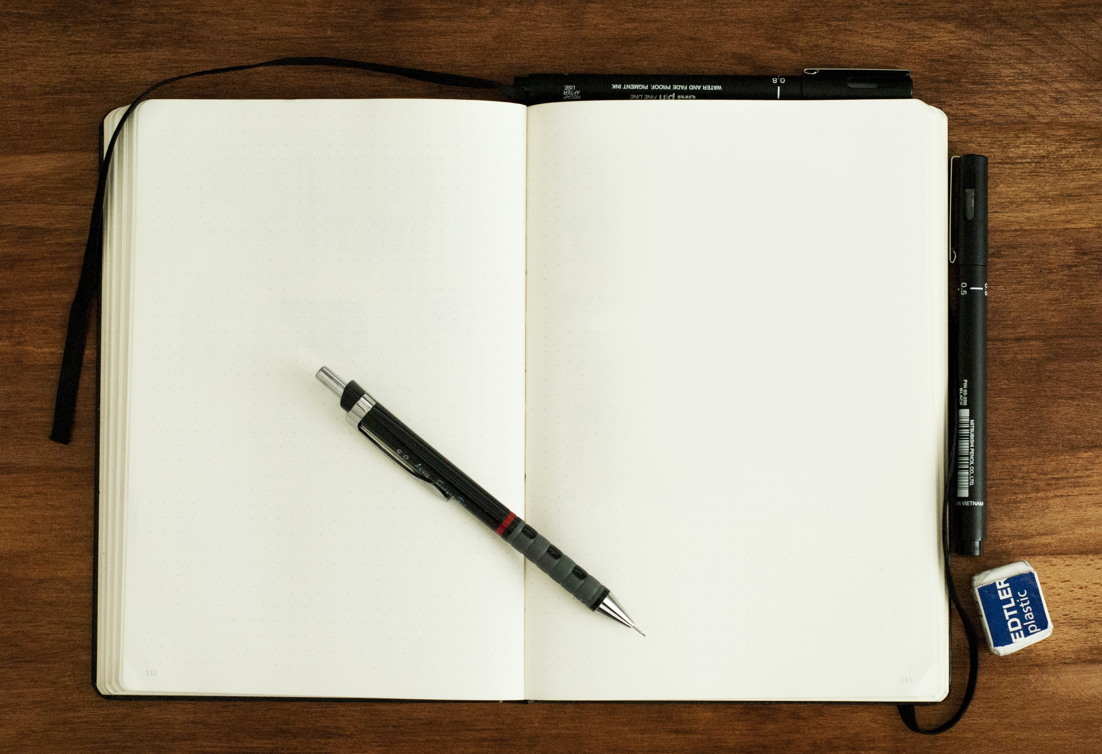 A journal open to a blank page on a table with three pens and an eraser