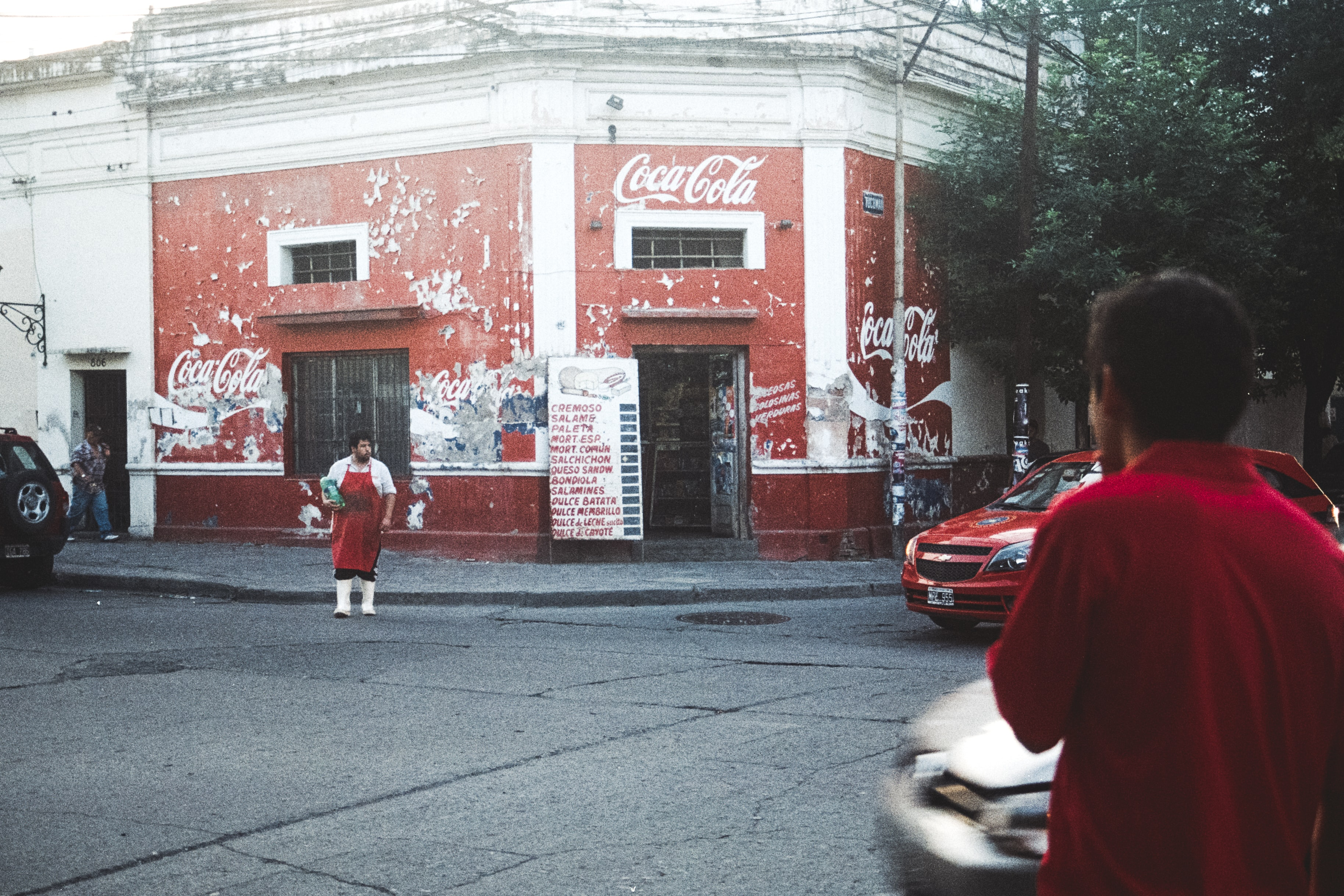A person in a red apron crosses the street outside a red shop with Coca-Cola logos