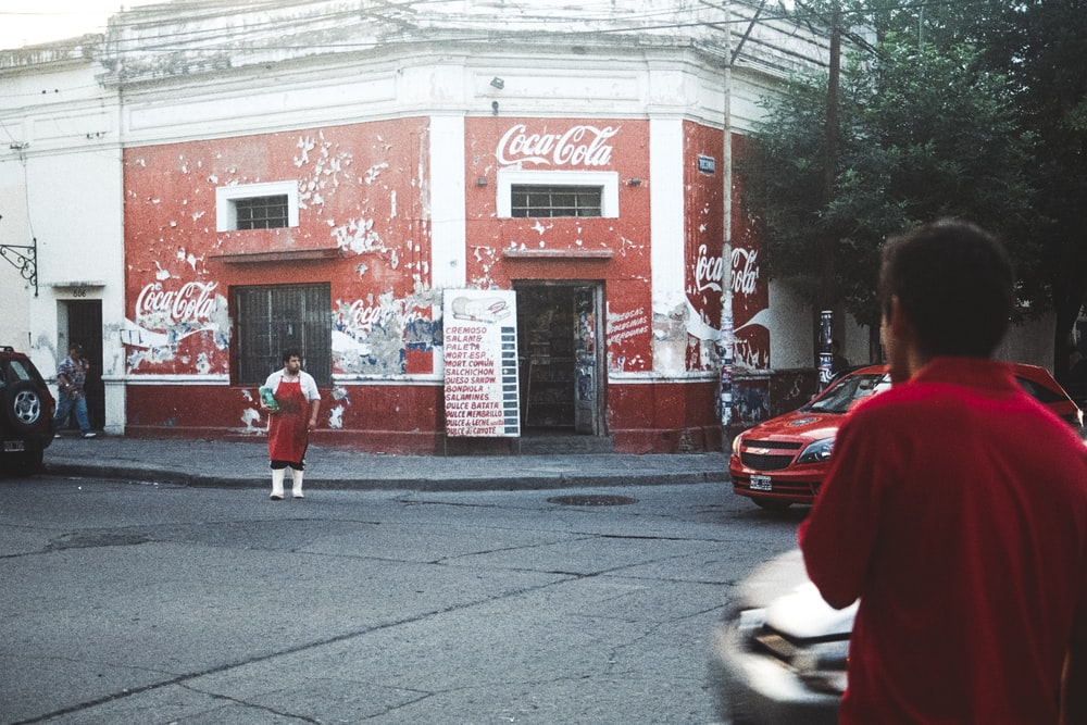man in red apron standing beside Coca-Cola building