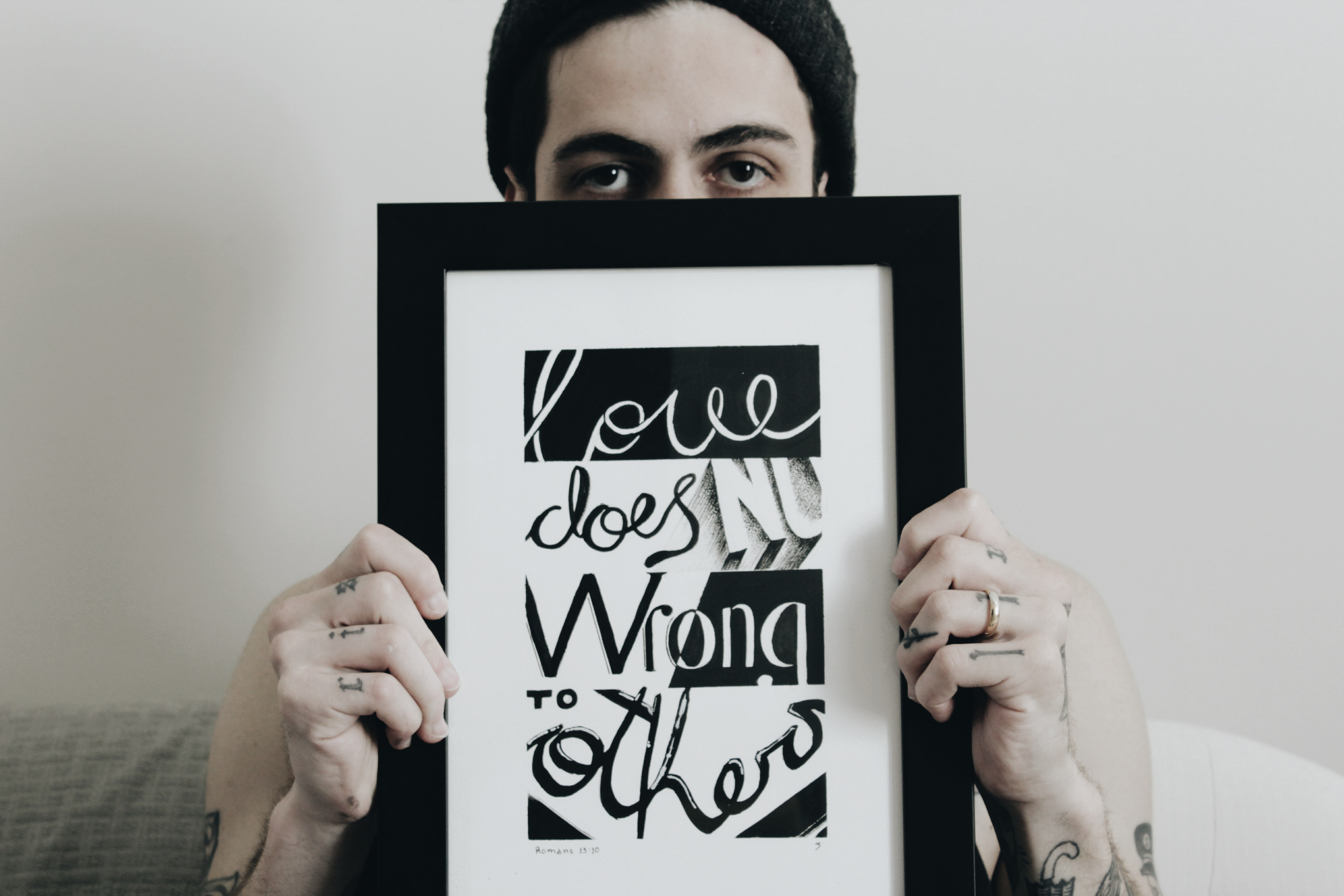 "A person holding a picture frame with writing inside that says ""Love does no wrong to others."""