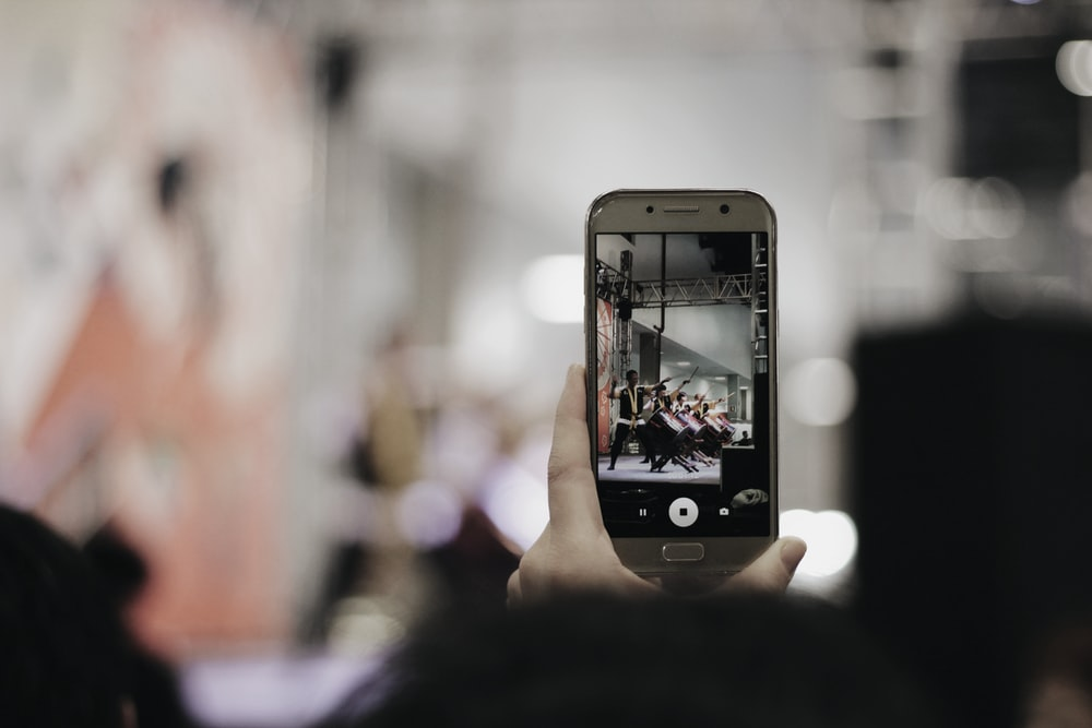 selective focus photography of person using silver smartphone